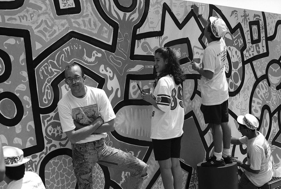 Teenagers in shorts paint a mural of graphic designs as a young man in glasses stands with arms folded looking at the camera.