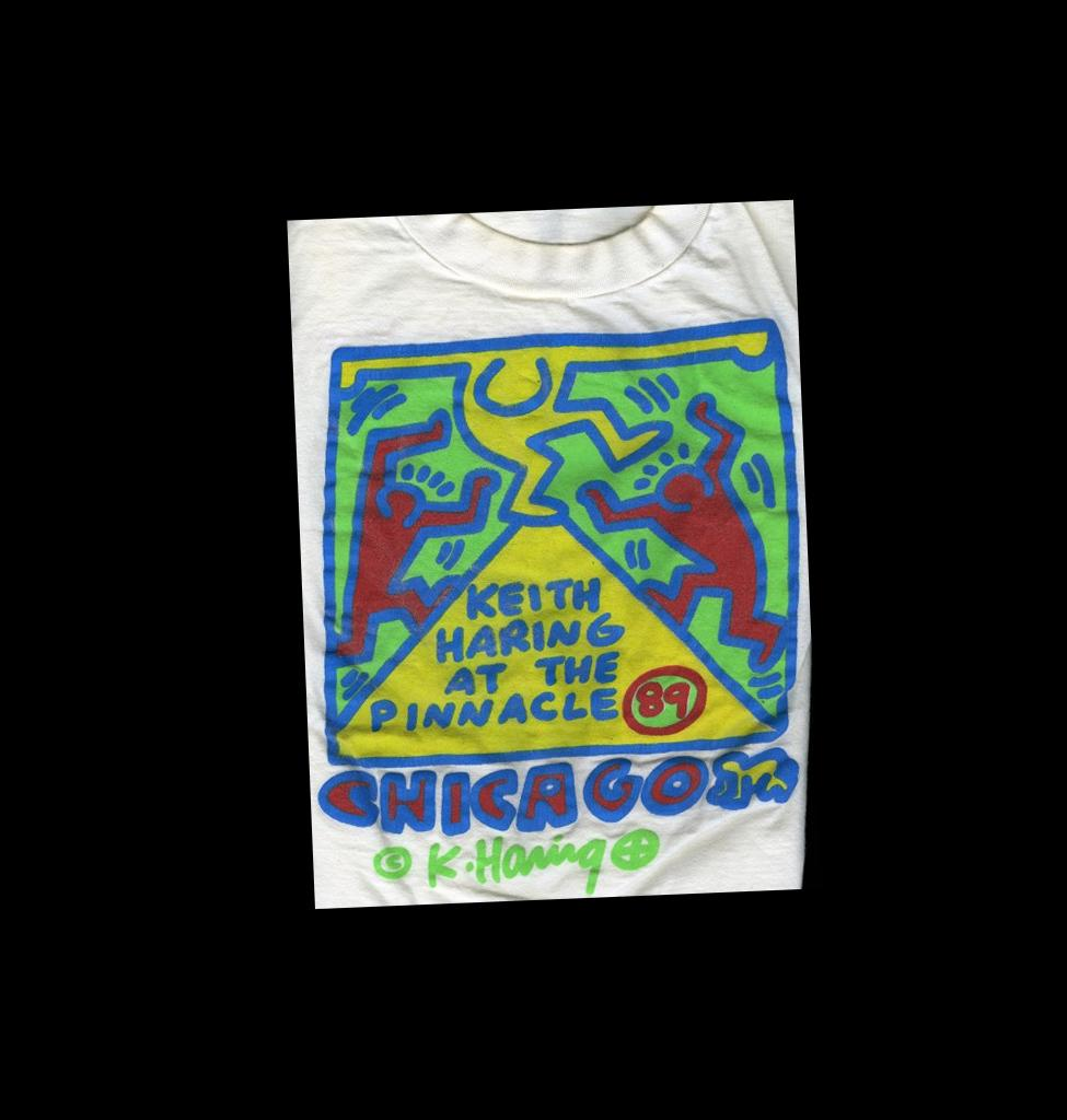 On a white tee shirt, three colorful cartoon figures dance on a yellow triangle inside a blue-outlined square with light green fill.