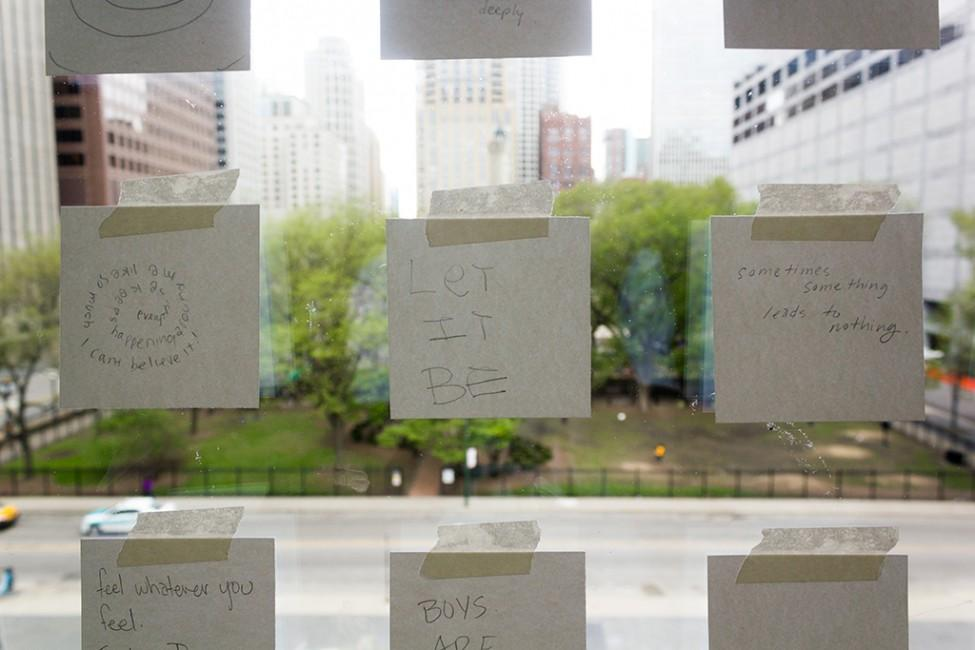 A three-by-three grid of white post-it notes with text taped to the front window of the MCA
