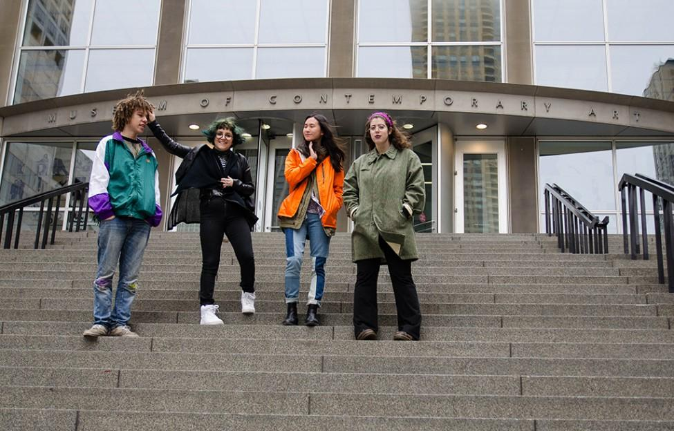 Four young adults pose playfully for a photograph on the stairs of the entrance to the MCA.