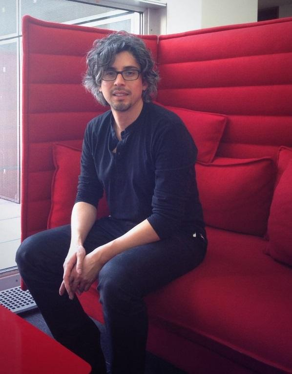 A man with wavy grey hair and glasses sitting on a high-backed red couch