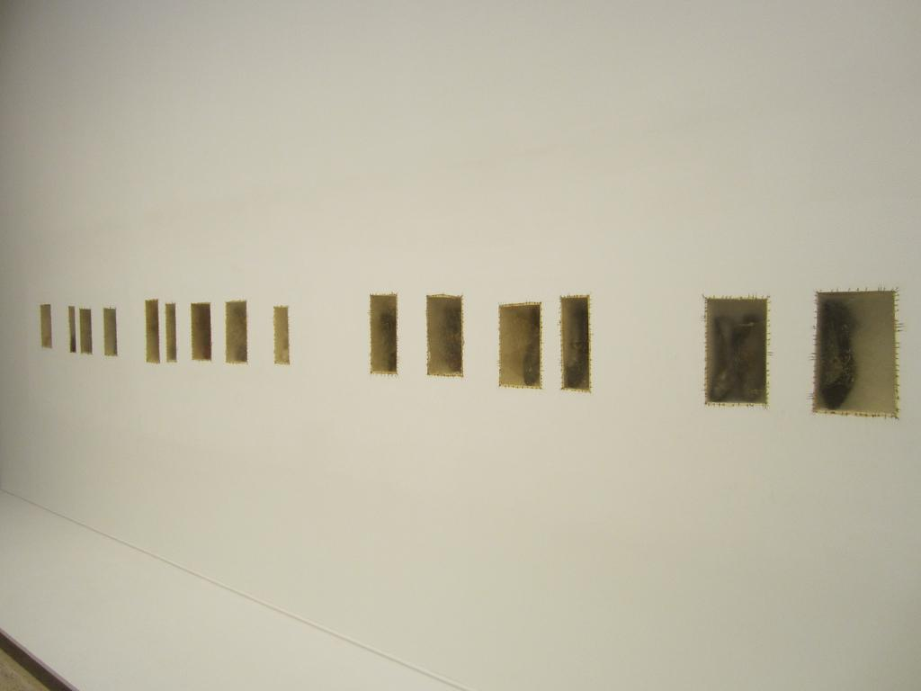 A wall displays several rectangular inlays with shoes inside of them, as if held in amber.