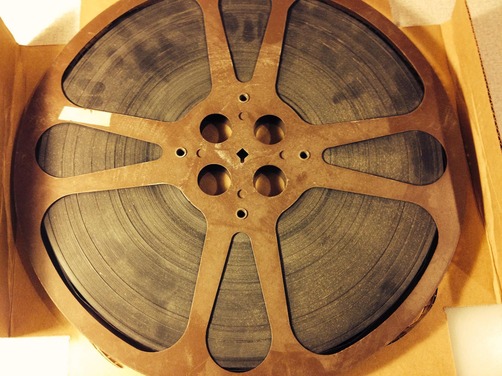 A rusty 16mm metal reel full of film sits in an open cardboard box.