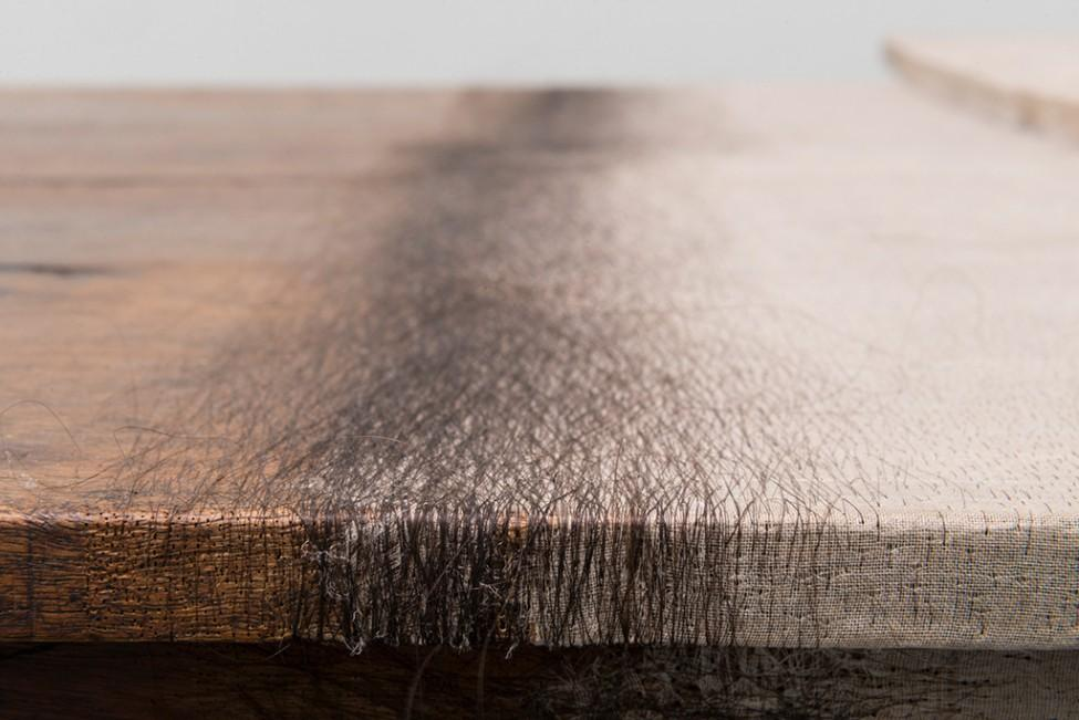 A close-up photograph shows a wooden table with the interwoven pattern of hair delicately matted into it.