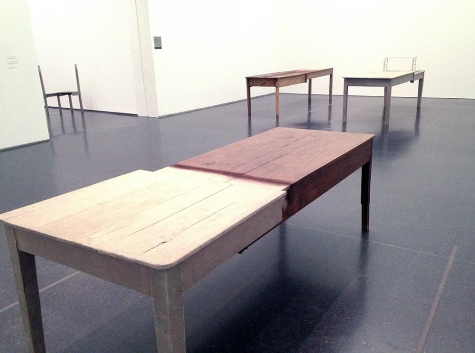 A room holds three tables, each constructed from two halves of different kinds of wood.