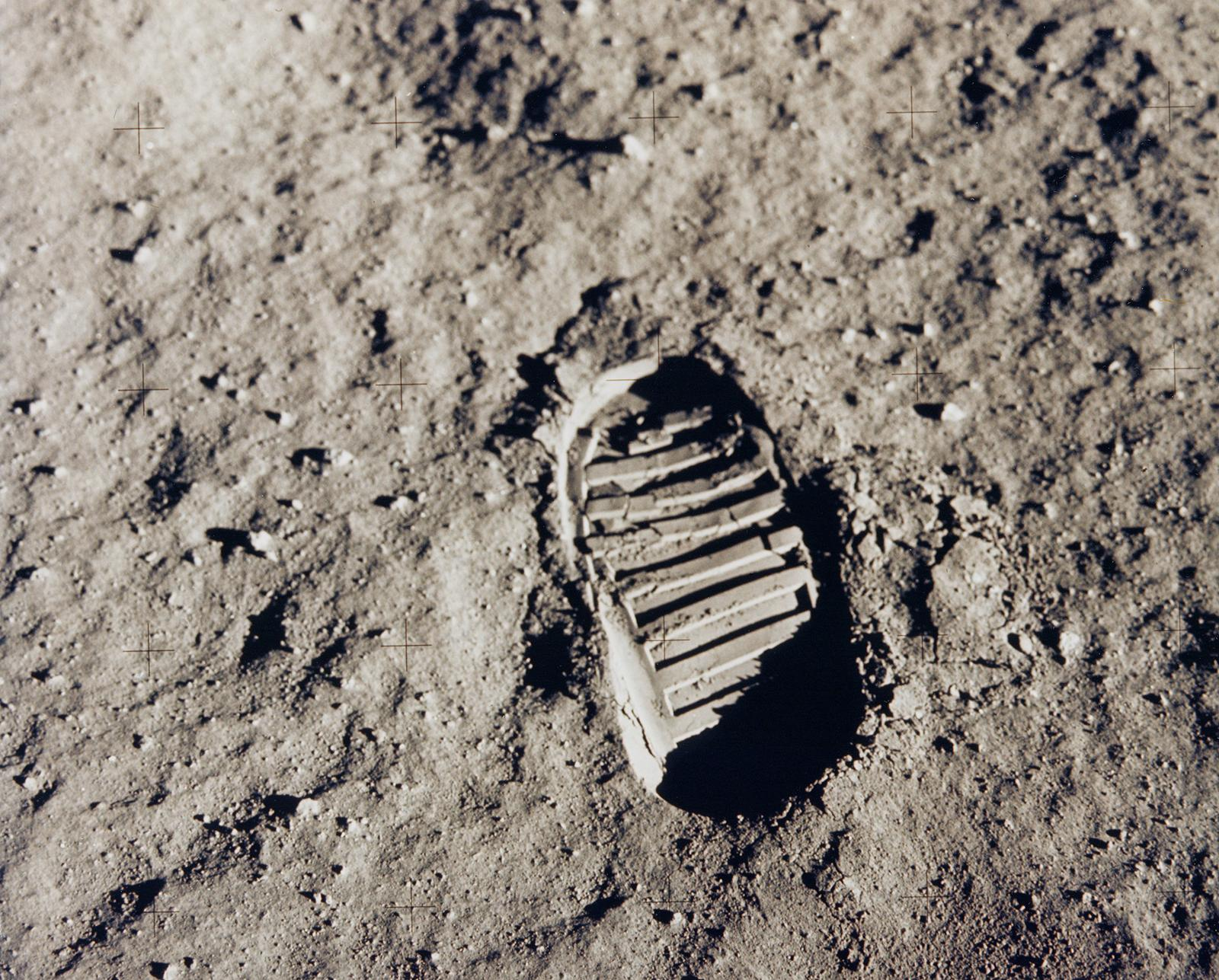 This sepia image of a boot print in moon dust is covered by a four-by-five grid of faint plus marks.