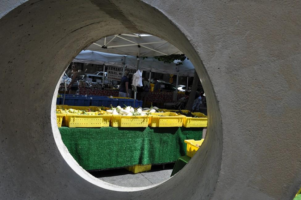 A table with yellow bins of vegetables seen through a circular hole in a large concrete sculpture