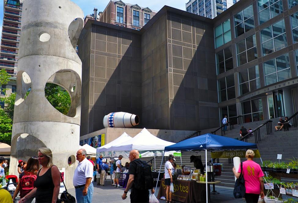 View of the MCA Plaza with two sculptures, a crowd of people, and farmers' market stalls