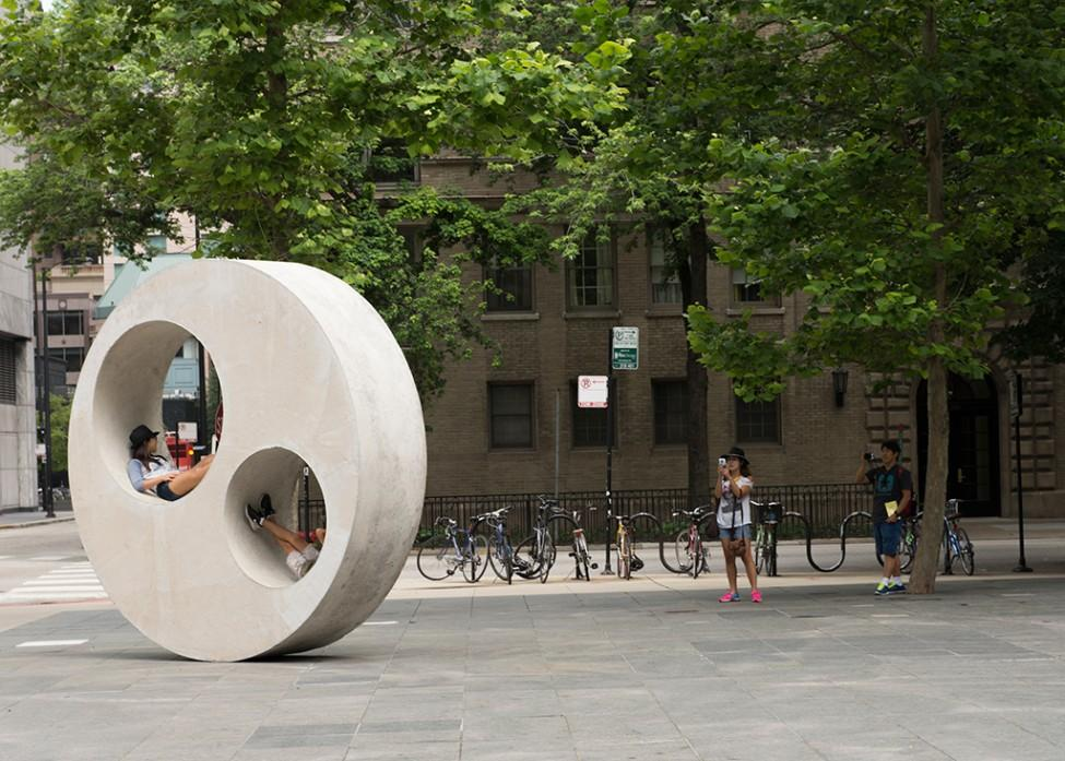 Teens lounging in two circle cutouts of a large circular concrete sculpture on the MCA Plaza