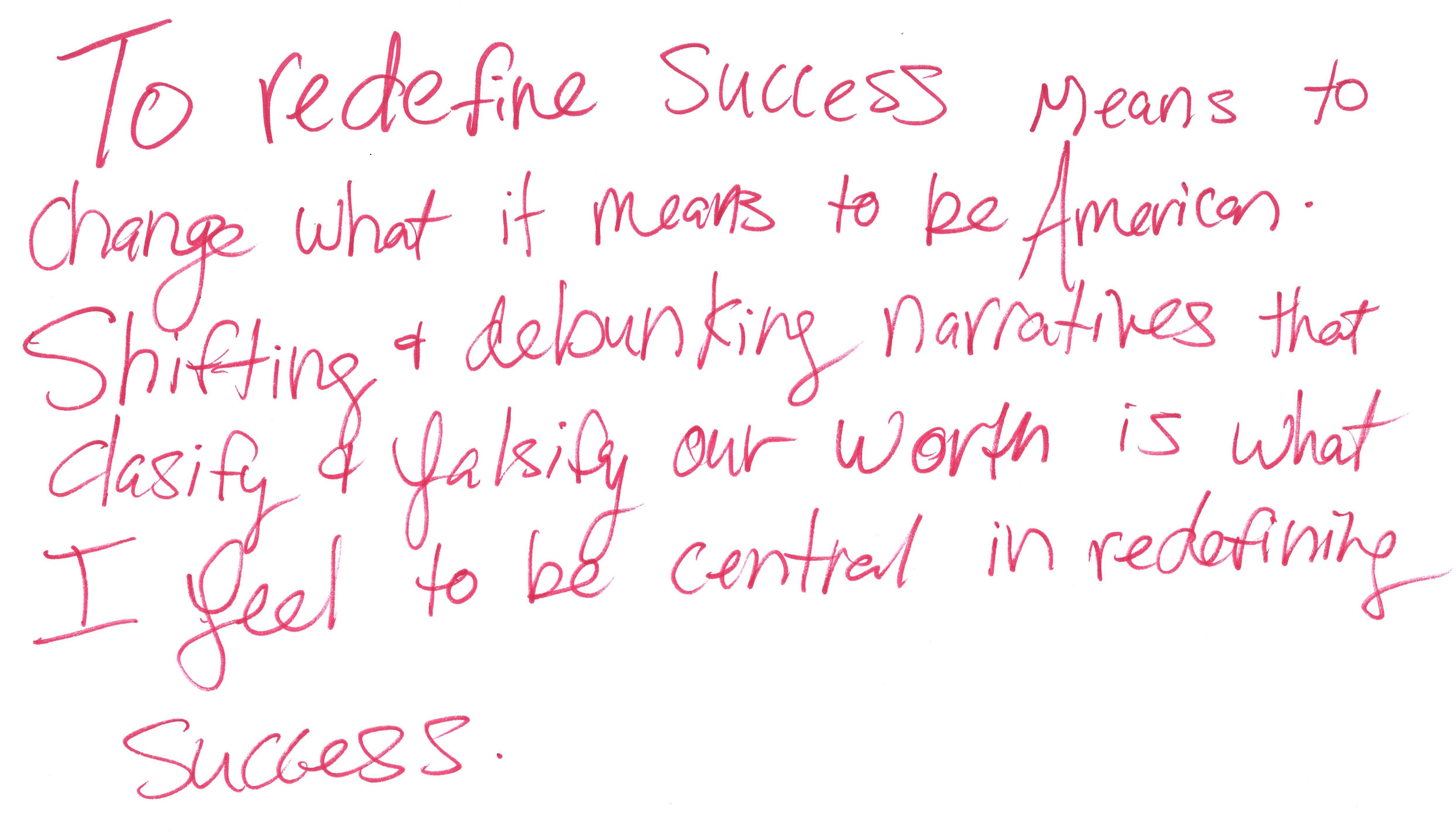 """Six lines of handwritten text in red marker read """"To redefine success means to change what it means to be American. Shifting & debunking narratives that clasify & falsify our worth is what I feel to be central in redefining success."""""""