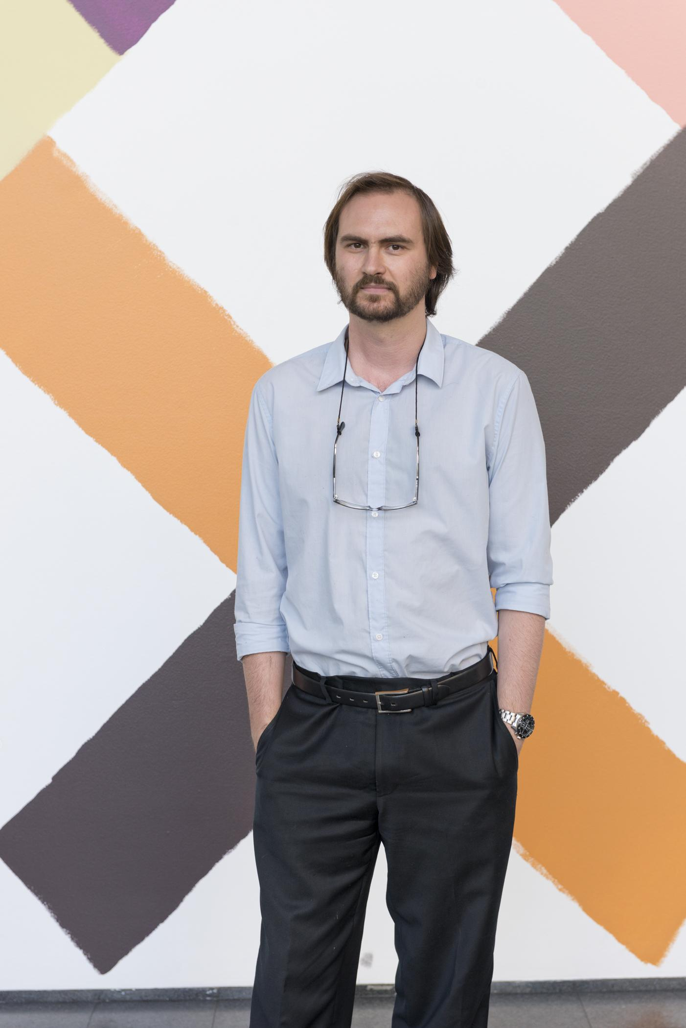 Former MCA curator Dieter Roelstraete stands in front of a wall painted with multicolor exes.