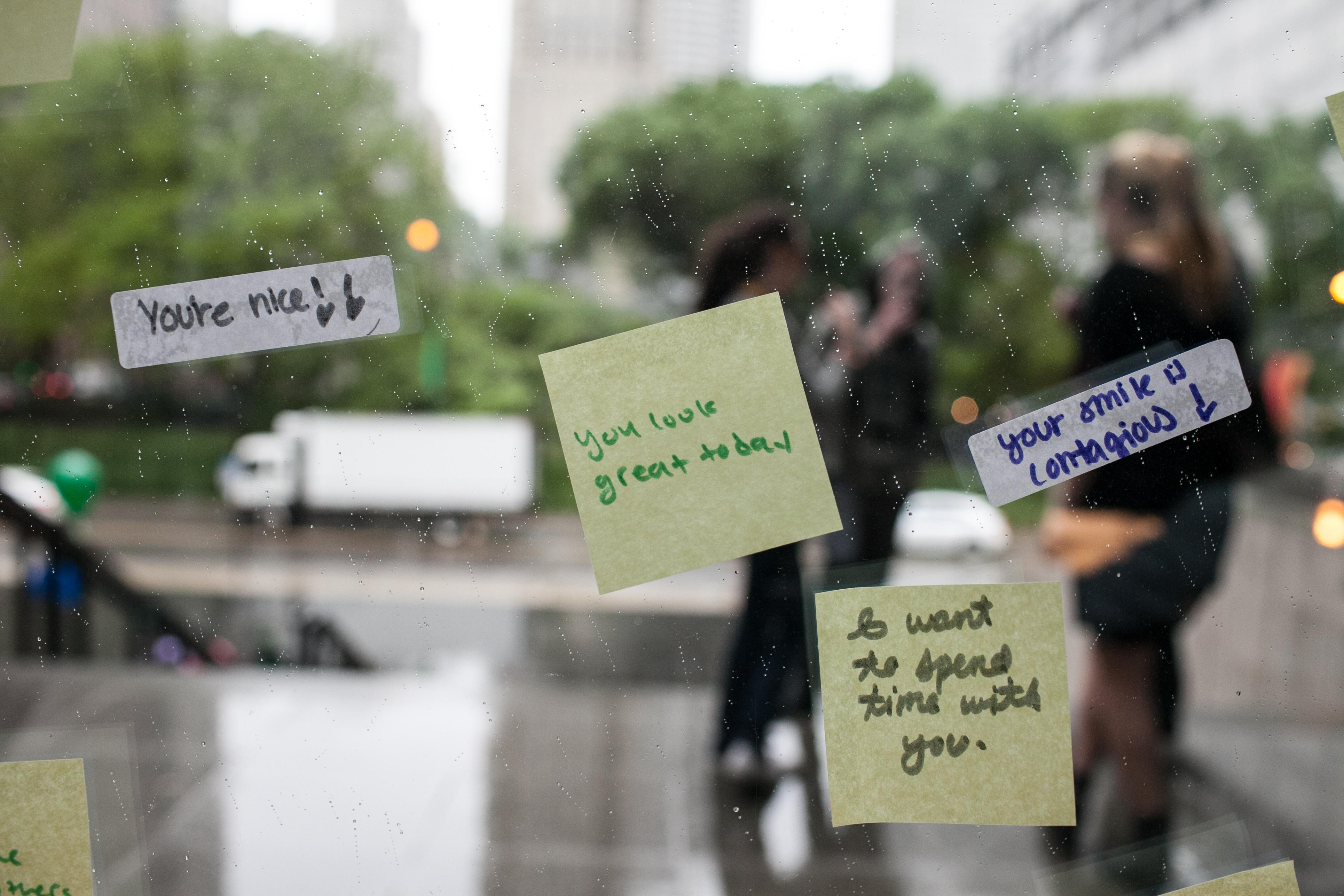 Post-It notes and stickers with complimentary phrases are stuck to a window looking out at people on the MCA's front staircase.