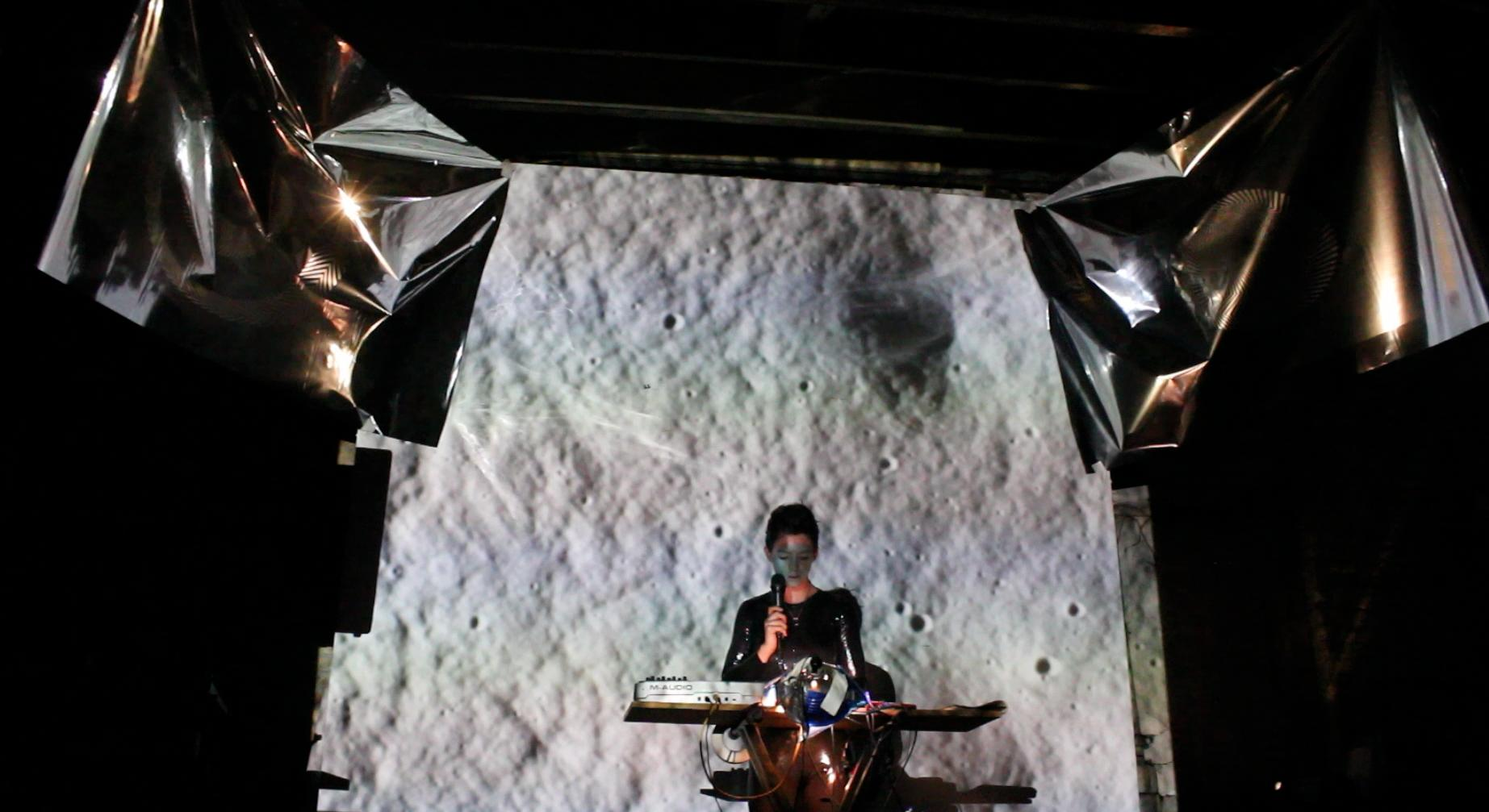 A person holding a microphone sits at an unusual desk with a large black-and-white backdrop that resembles the cratered surface of the moon. Two crinkled metallic sheets are suspended above.