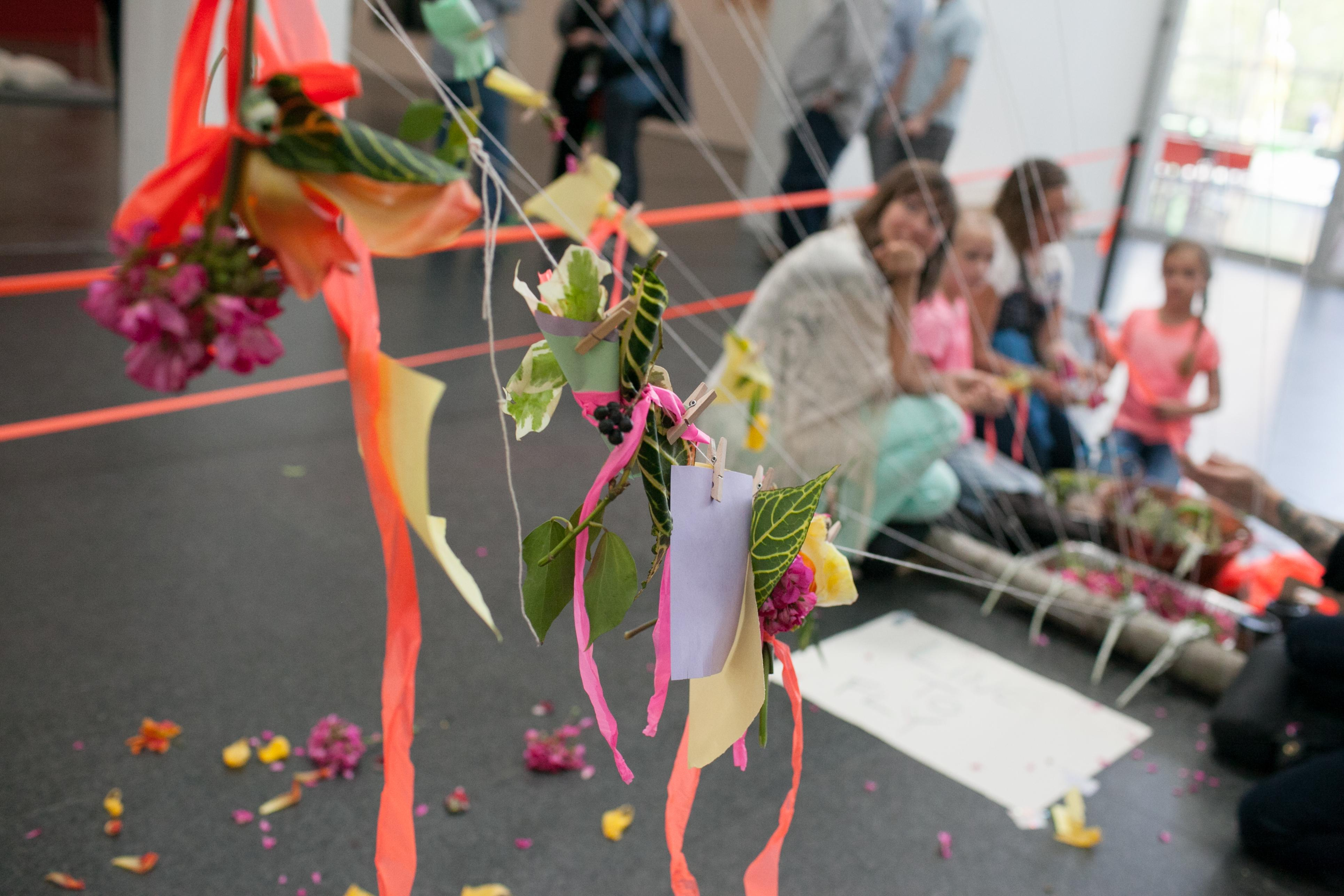 Adults and kids look through an installation of fake flowers and ribbons attached to strings with clothespins in the MCA's Atrium.
