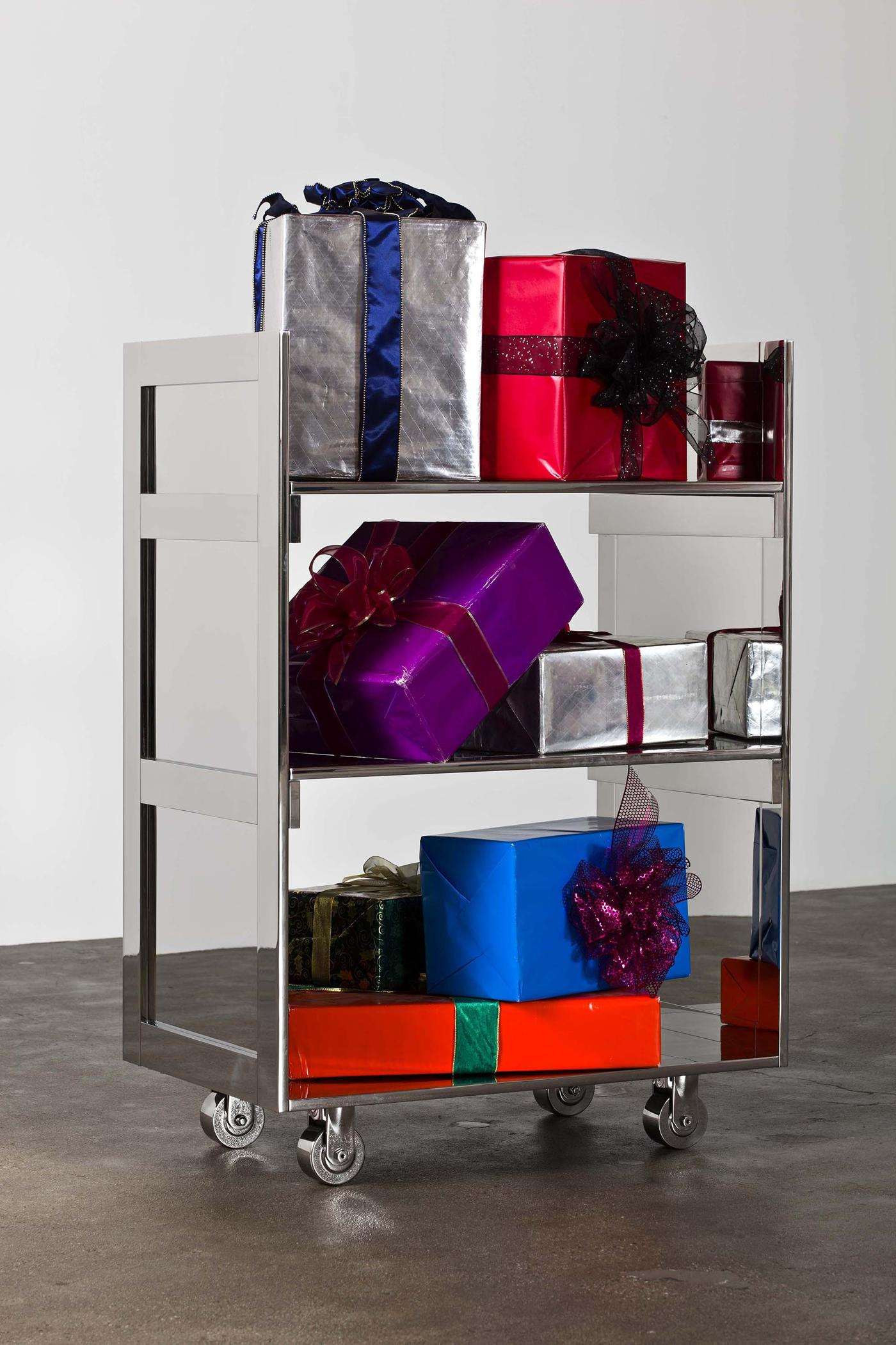 A three-tiered silver metallic cart holds colorfully wrapped gift boxes with bows.