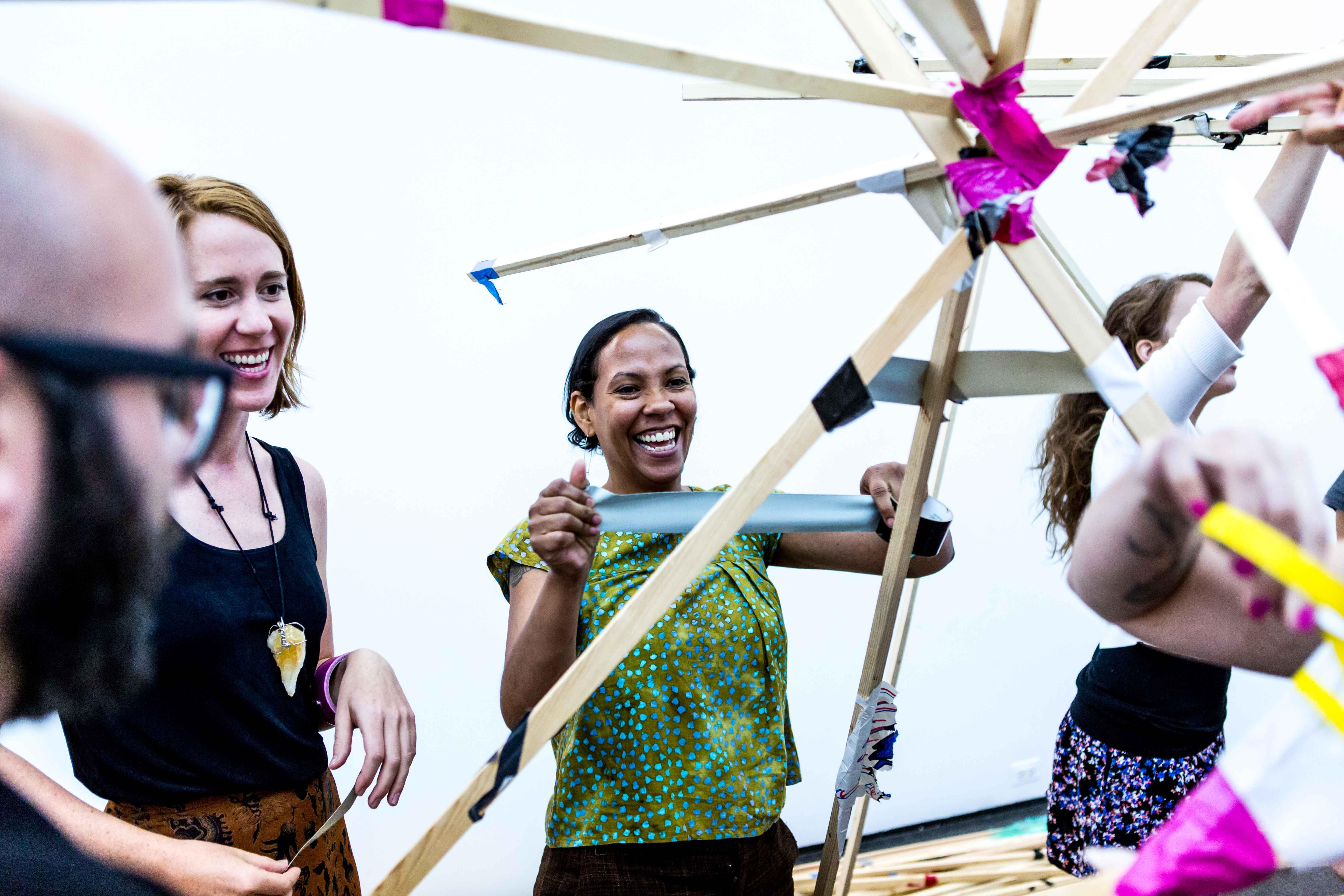 People making a structure with tape and long beams of wood