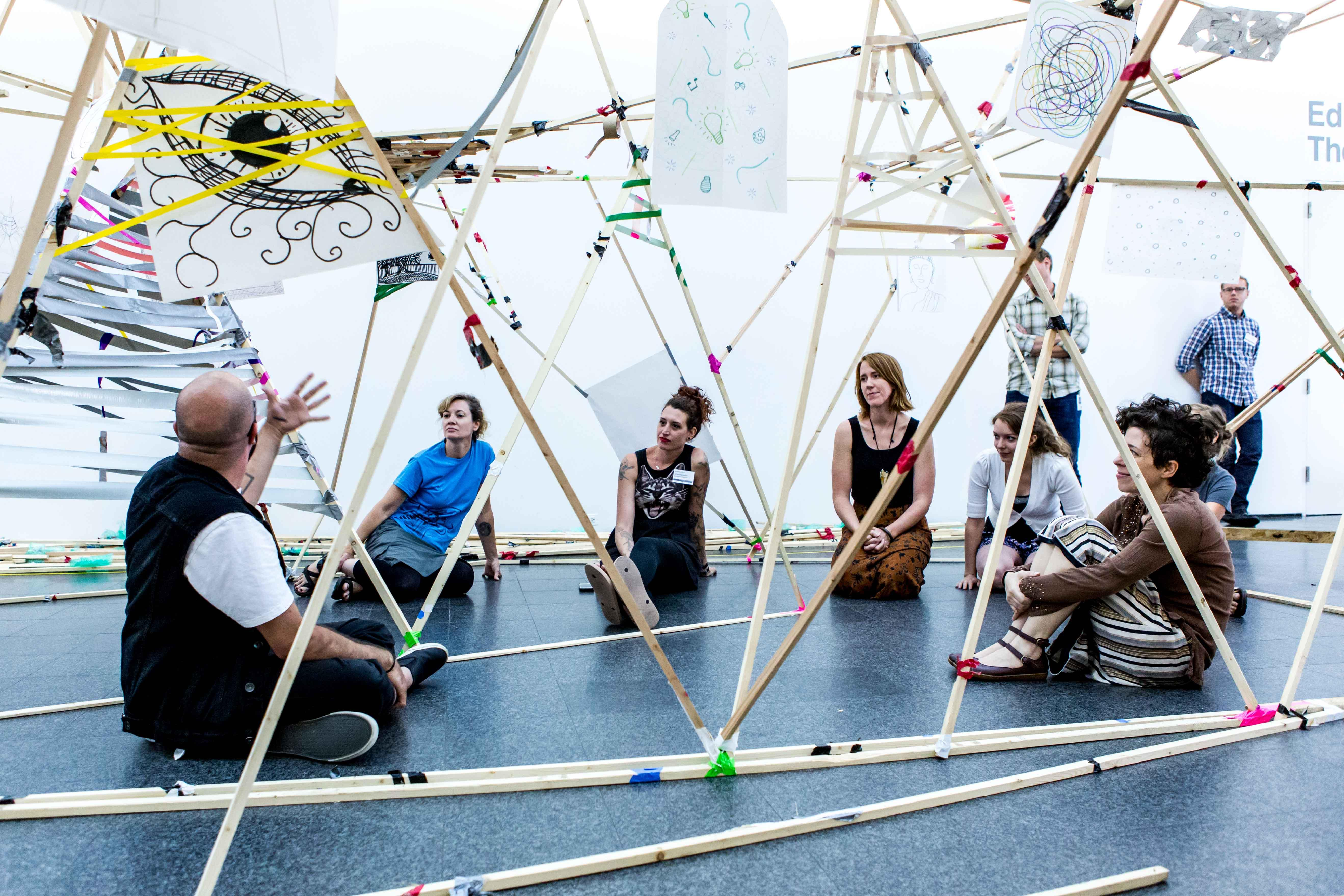 People sit on the ground in an open-air structure made of long wooden beams and tape