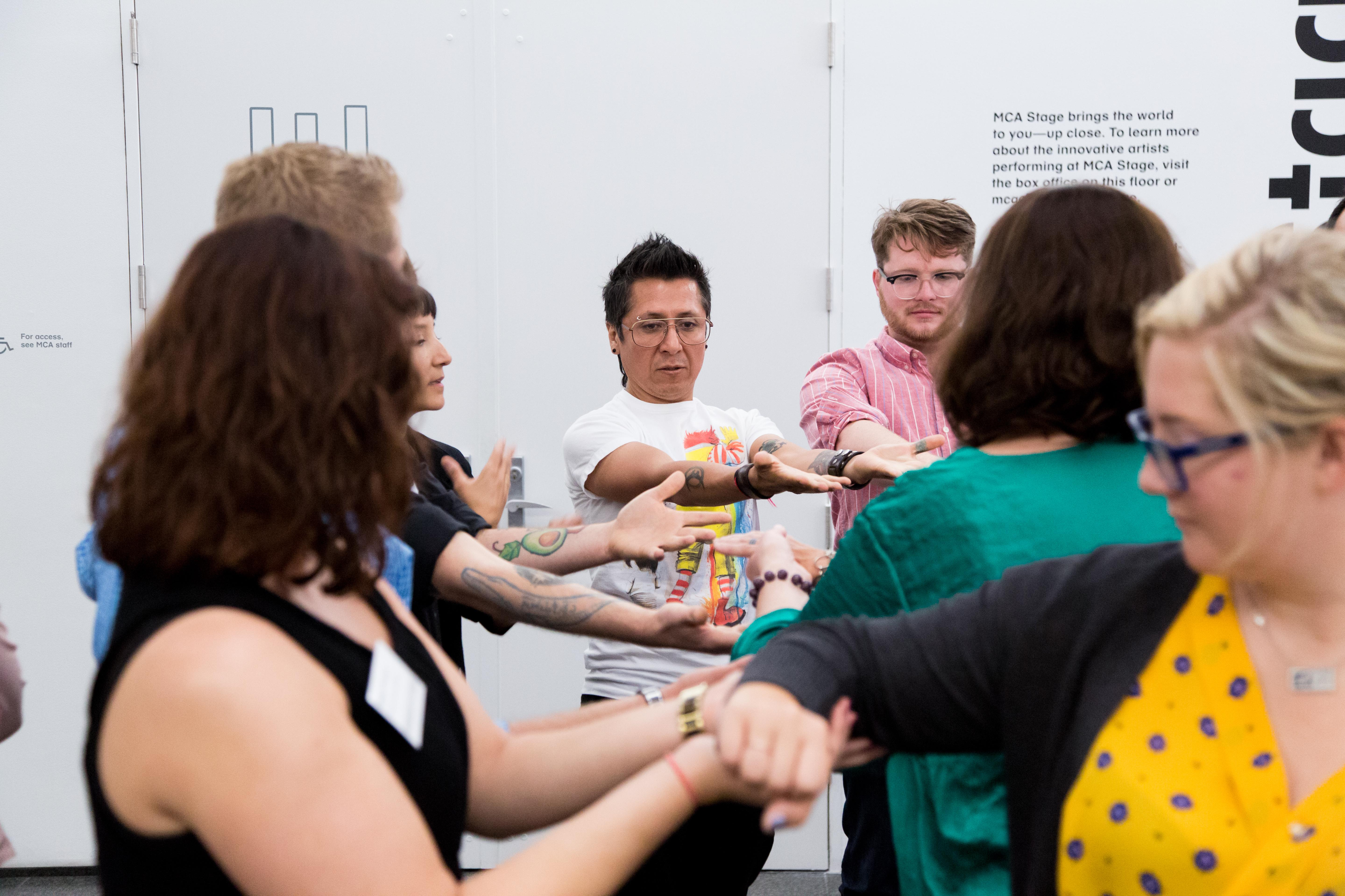 A group of adults, arms outstretched, participate a group activity.