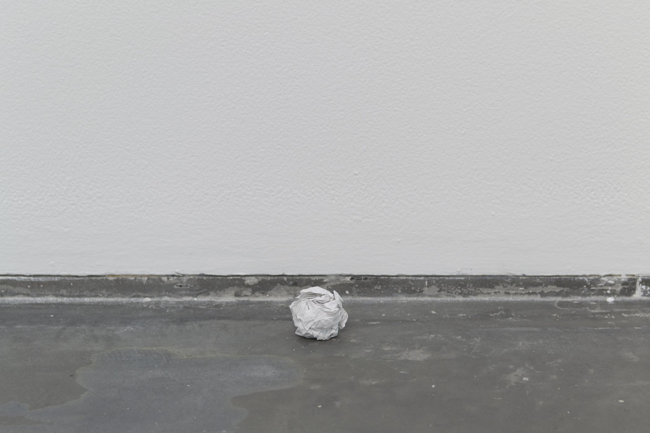 A white crumpled ball of paper on a grey floor near a white wall