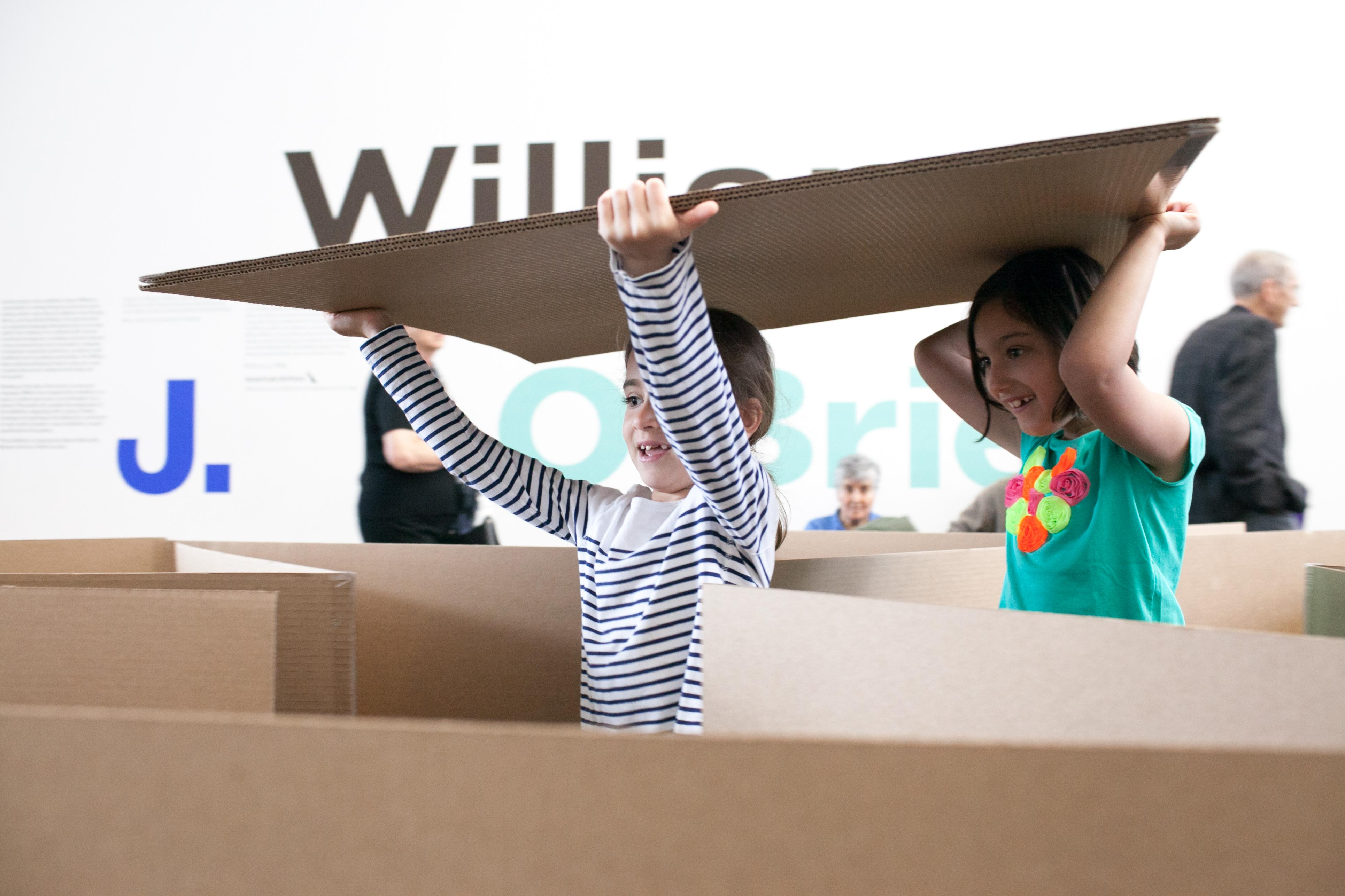 Two girls carry a sheet of cardboard above their heads as they wander through a cardboard maze. Their eyes are filled with wonder as they explore the maze.