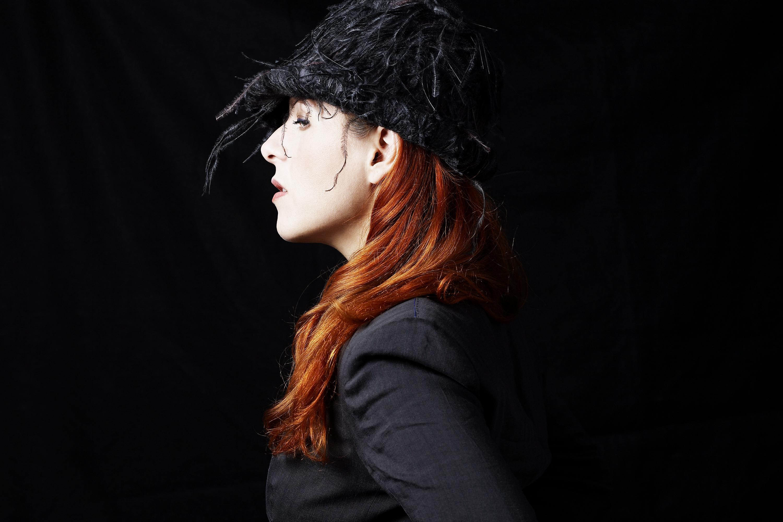 A close-up portrait shows musician Neko Case in profile.