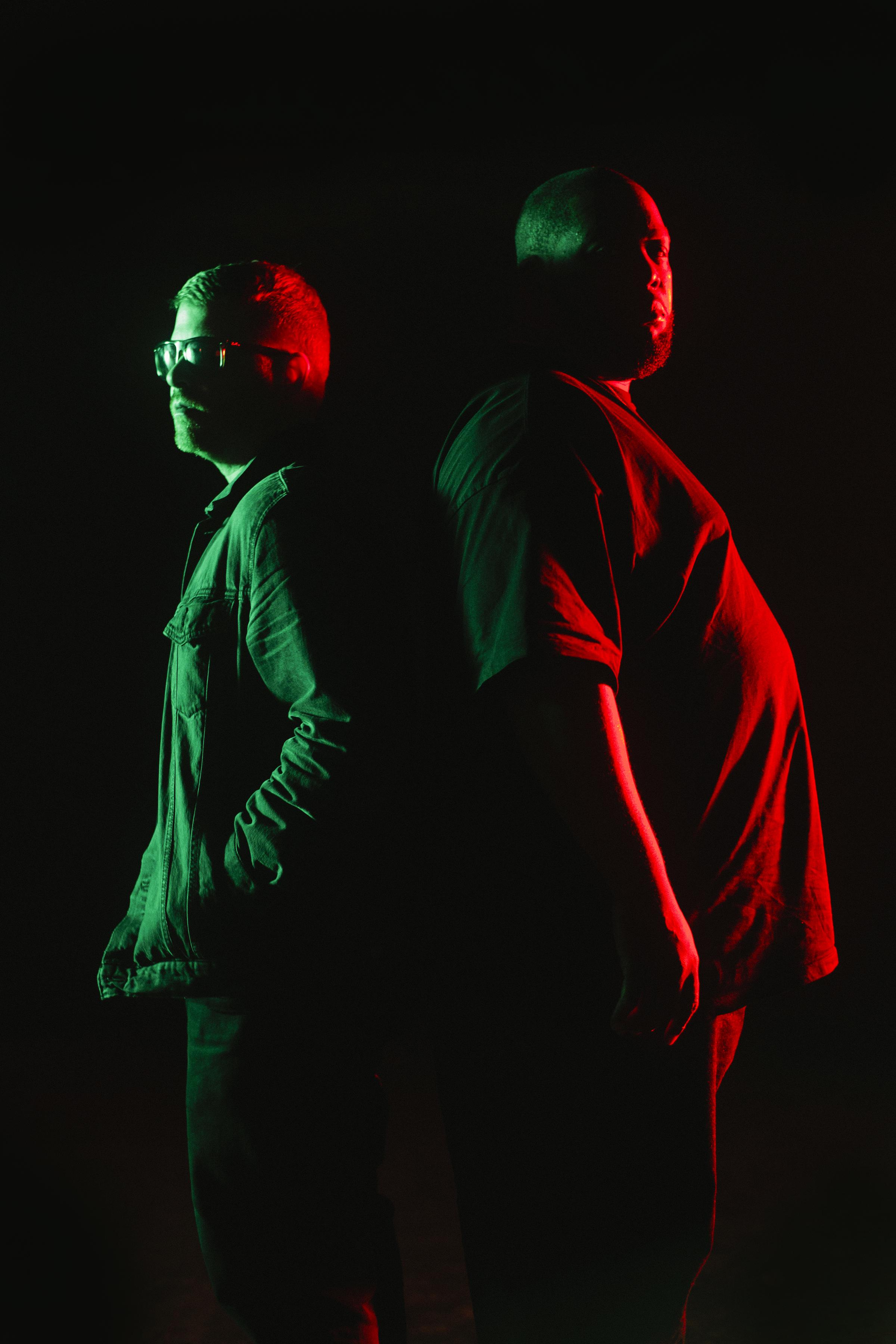 Two men standing back to back in a pitch black room are partly illuminated by a green and red light.