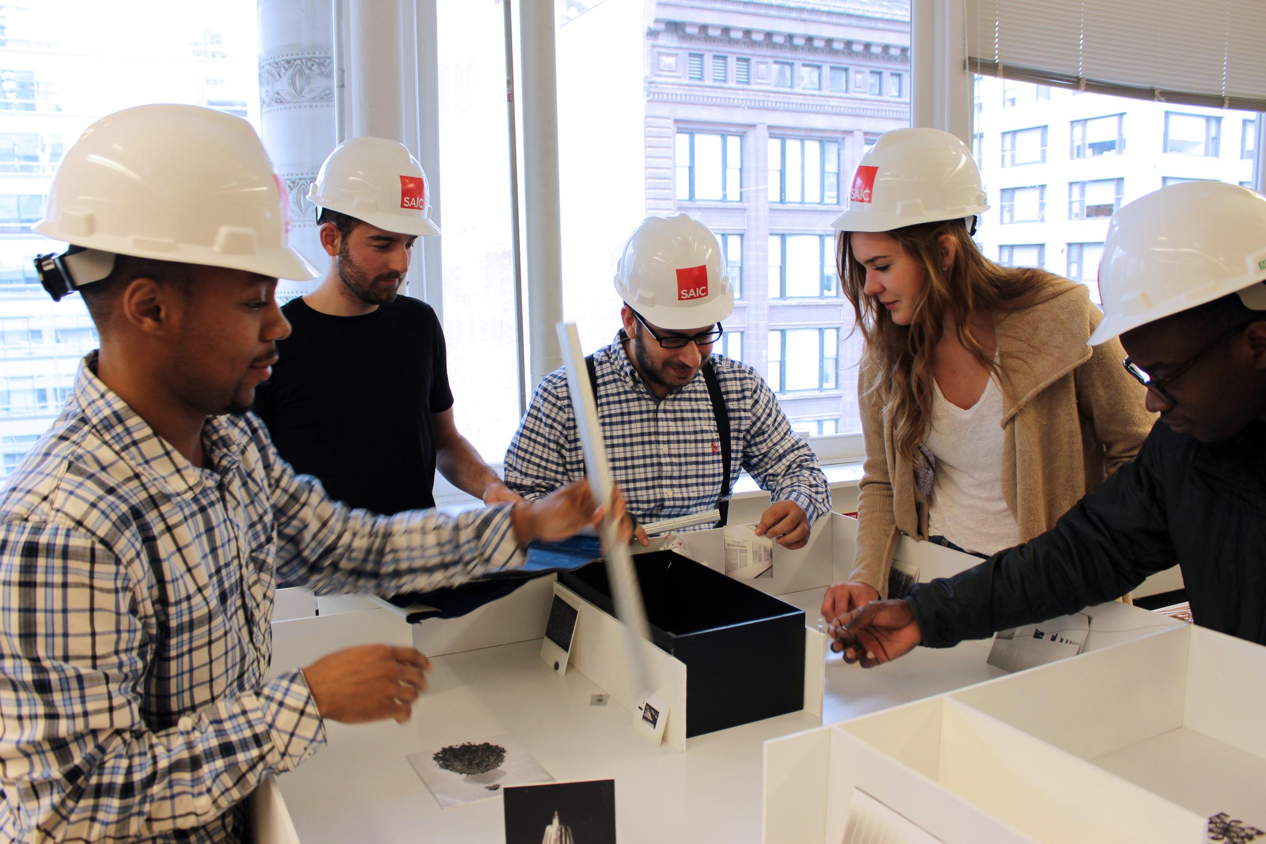 Five people wearing hard hats work on a model of the MCA's galleries.