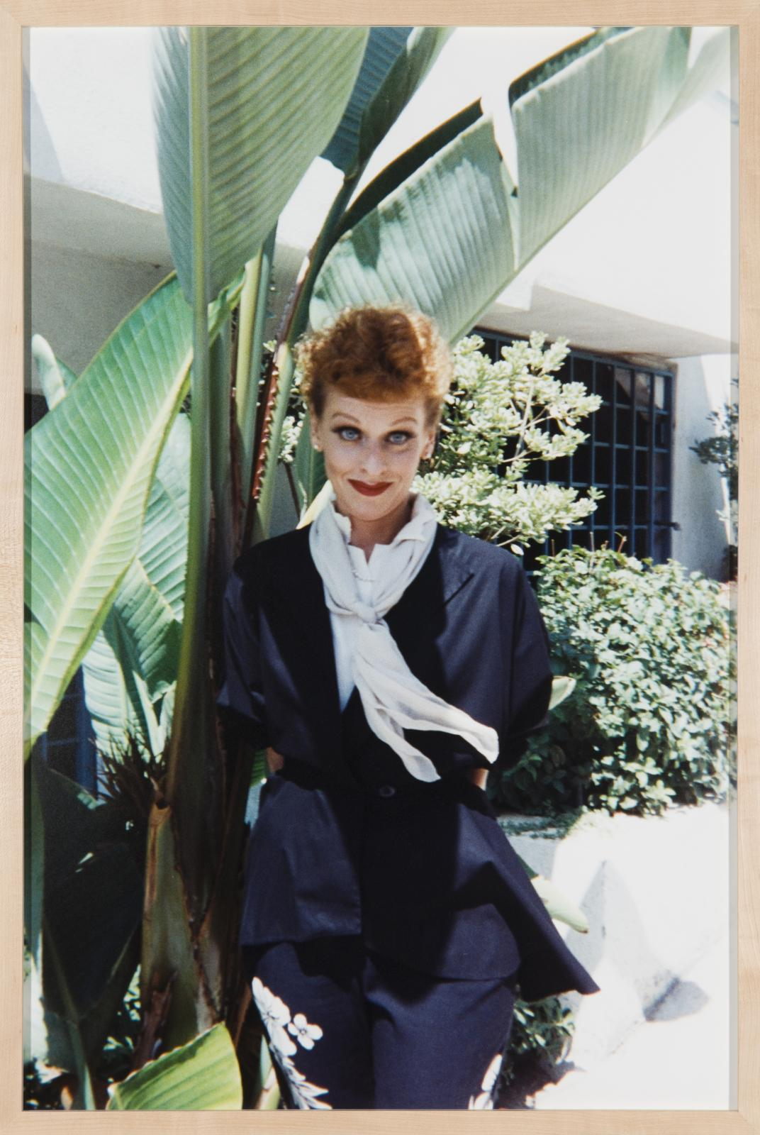 A person, dressed as Lucille Ball, stands next to a bird of paradise plant and other shrubbery near a brightly lit building.