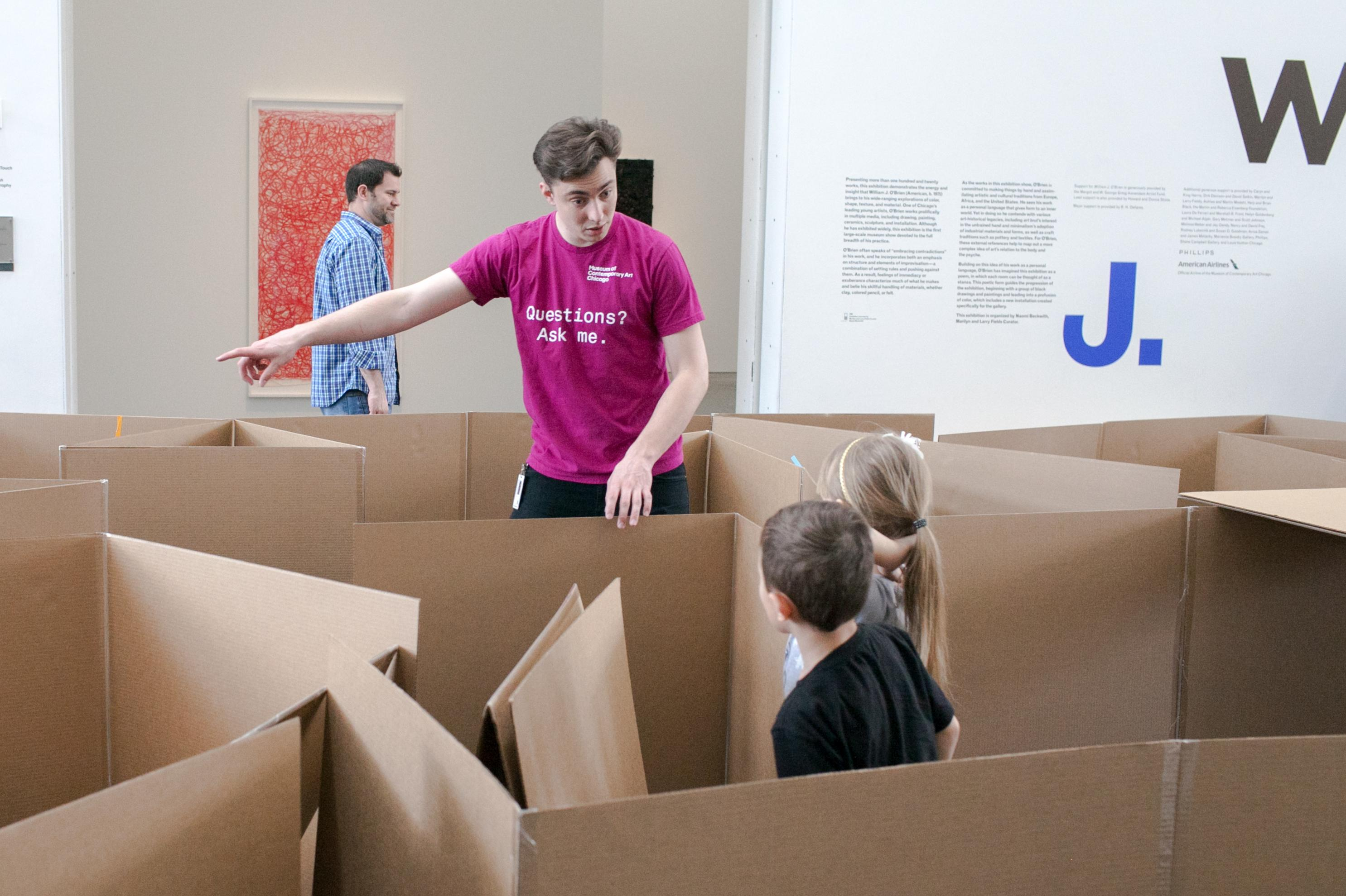 Two children in a cardboard maze look at man pointing to our left.