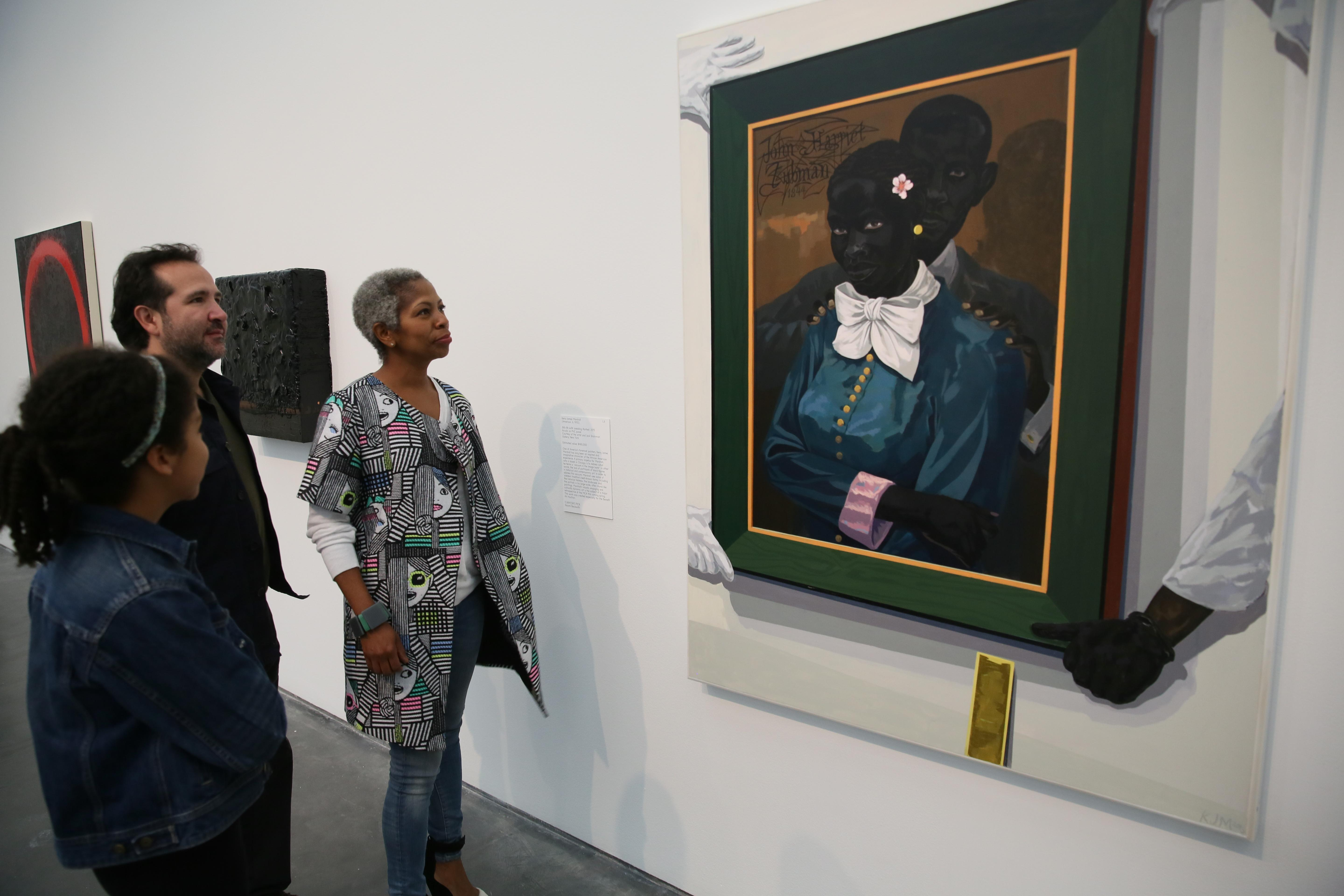 Three visitors look at a large painting, which depicts a painting of Harriet Tubman and her husband. The painting shows the portrait being held in place by men wearing gloves with a yellow level propped against the wall below.