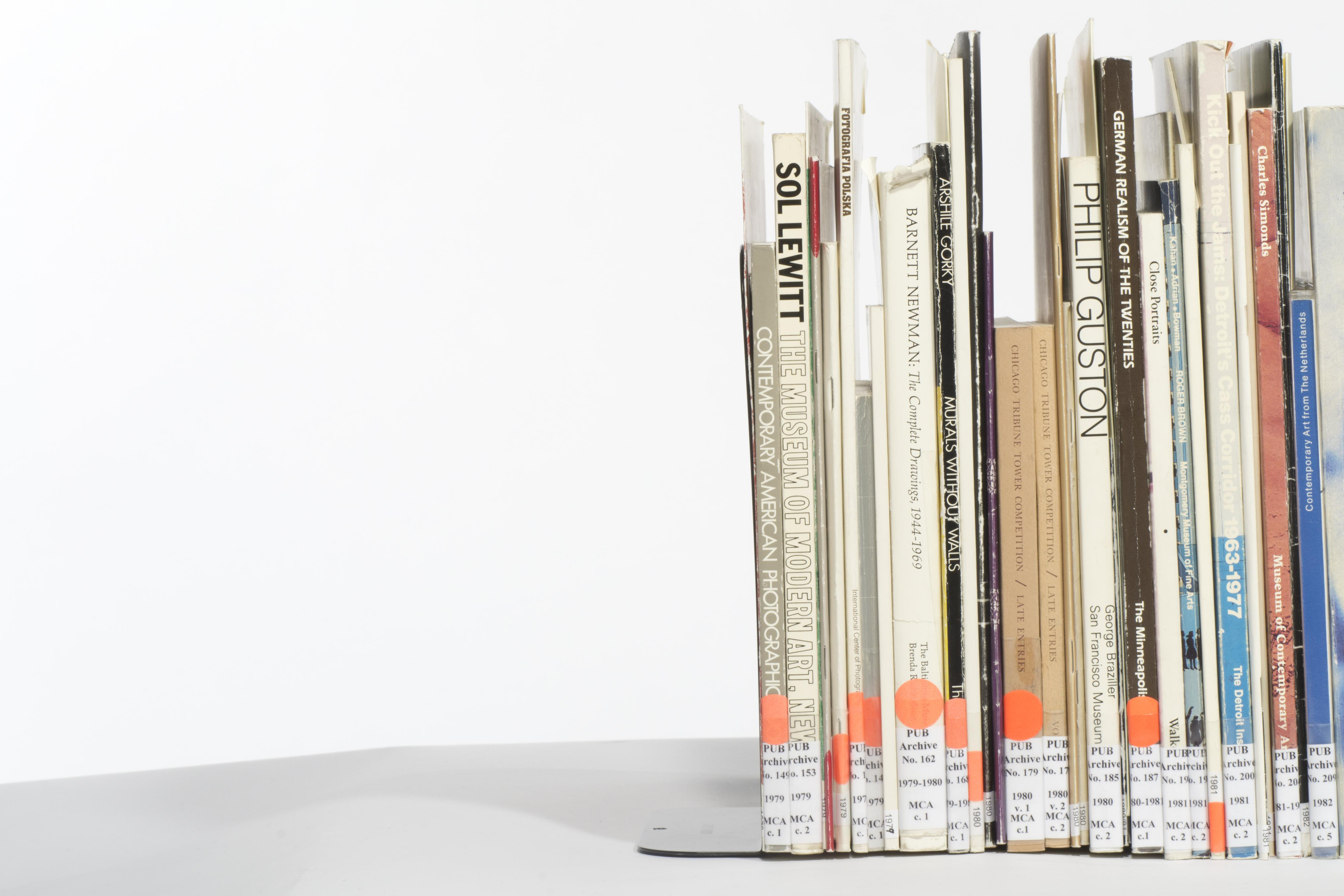 A group of catalogs with library call numbers are lined tightly next to one another on the right side of the frame.