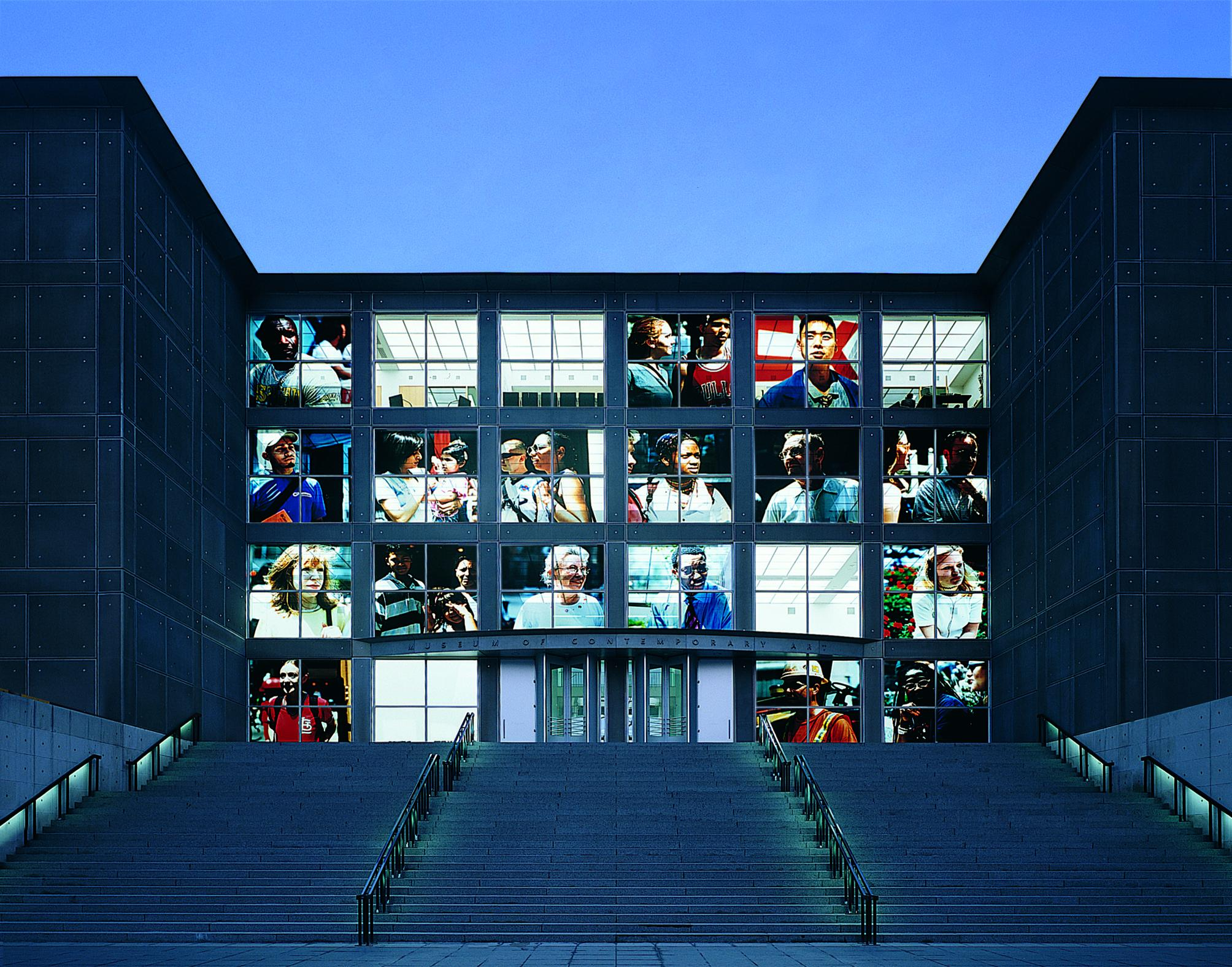 The front windows of the MCA illuminated with large close-up photographs of people.