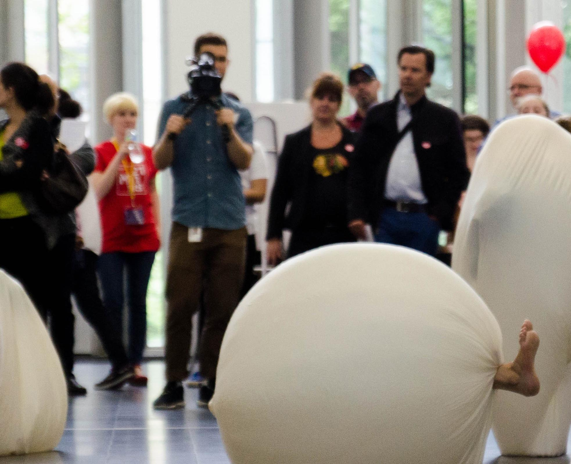Visitors gather around performers in large cloth spheres while a cameraman films the scene.