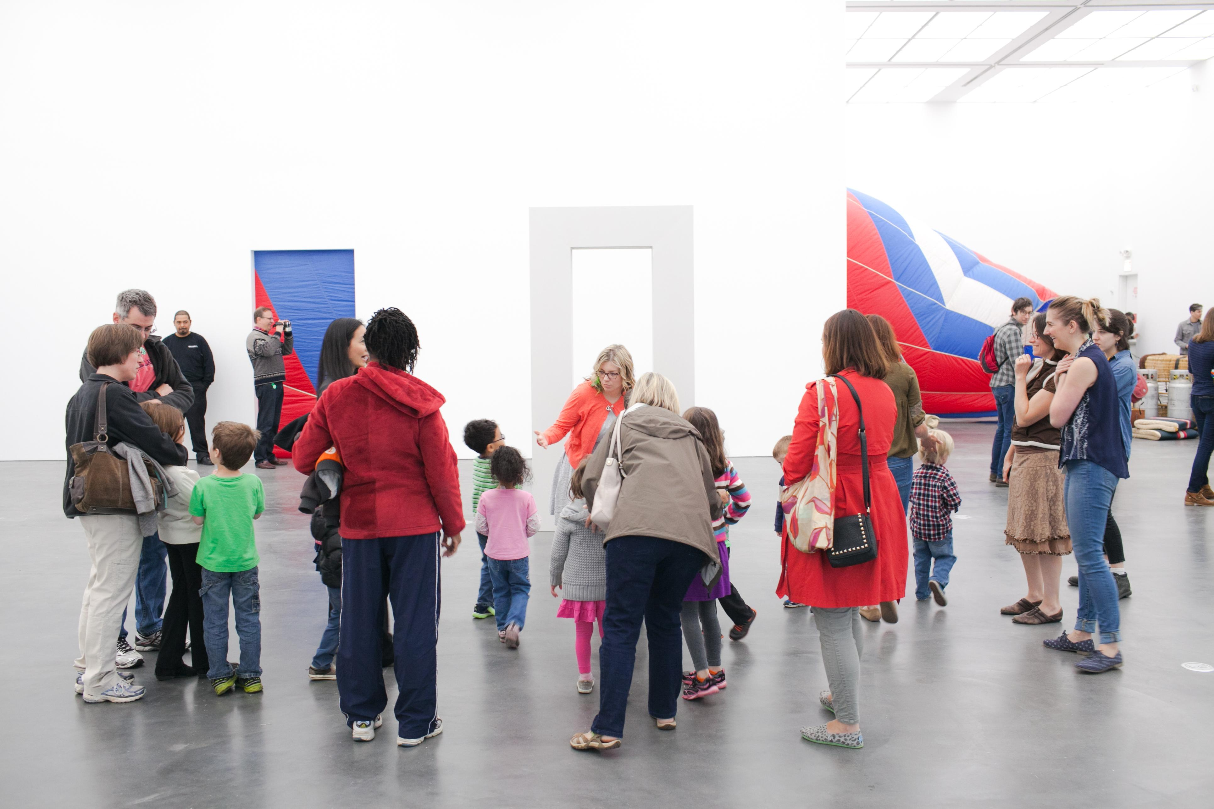 A large group of children and adults gather around a freestanding doorway-like sculpture in a brightly lit gallery space.