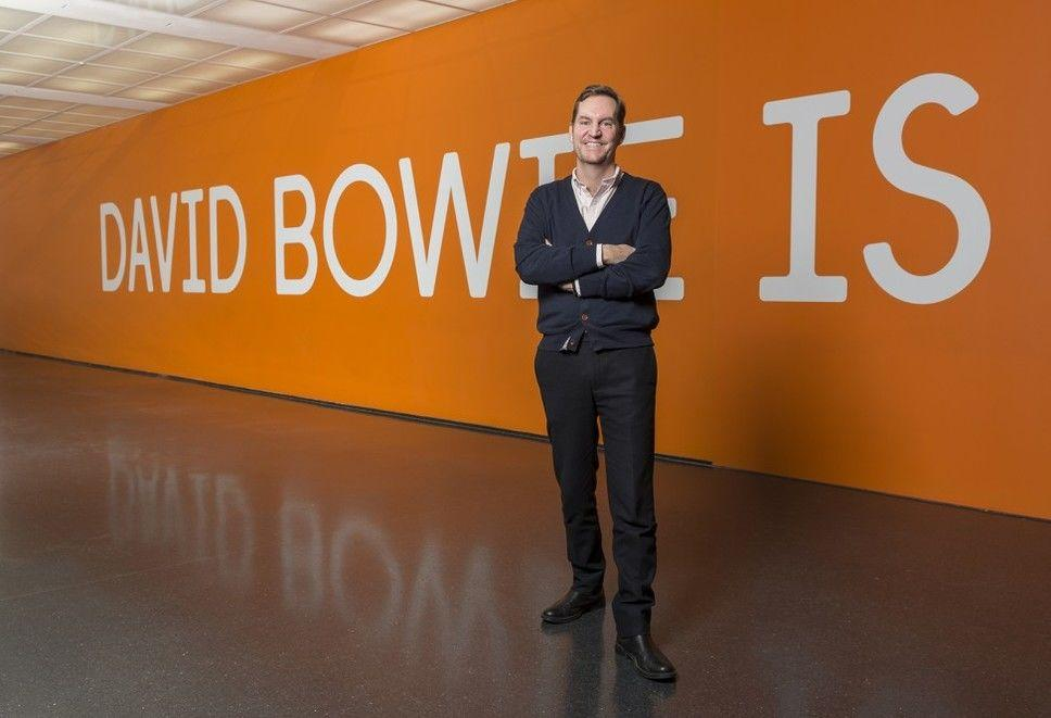 """James W. Alsdorf Chief Curator Michael Darling poses with a smile in front of the title wall for """"David Bowie Is""""."""