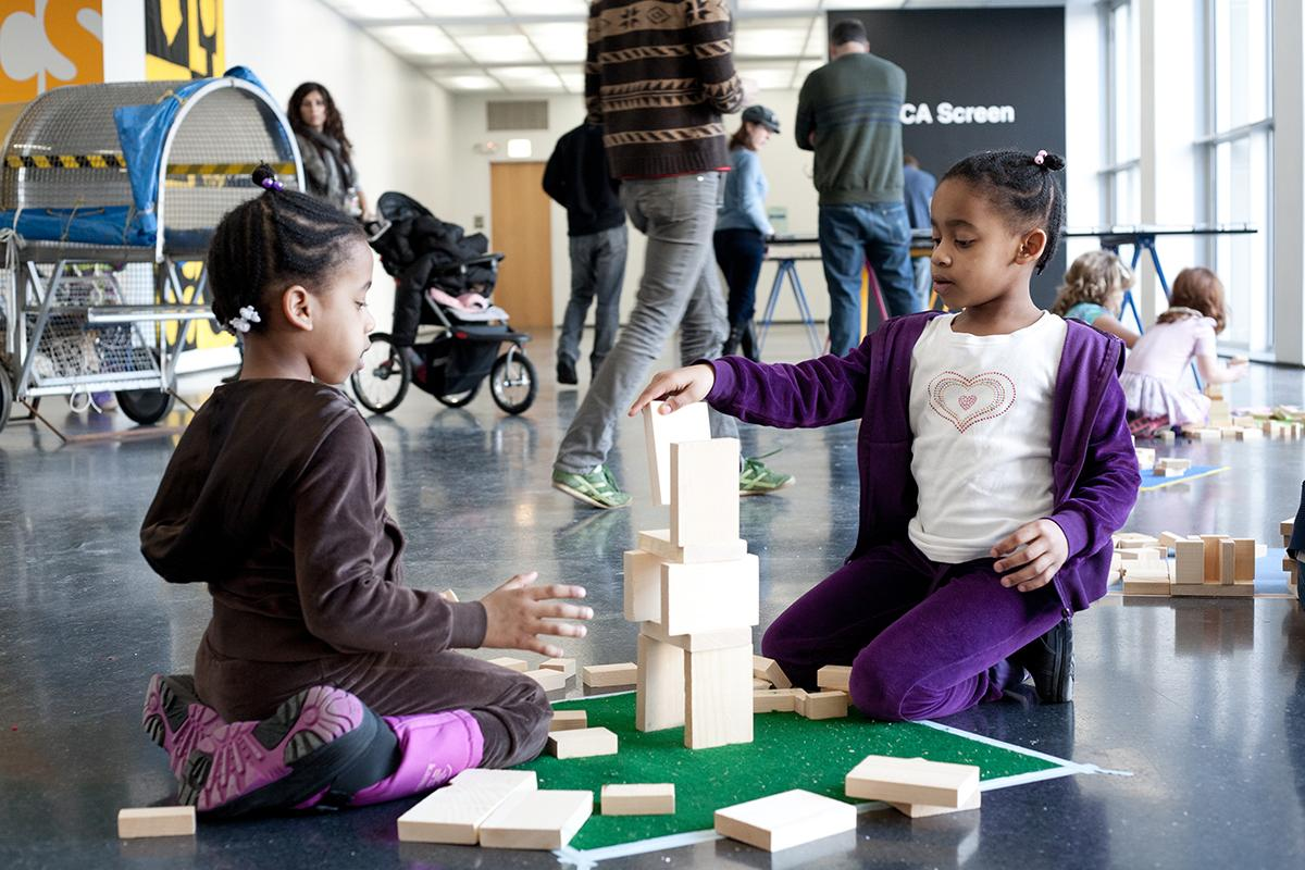 With families in the background, two dark-skinned young girls wearing tracksuits kneel in the MCA's fourth-floor atrium building a tower with rectangular pale-wood blocks.