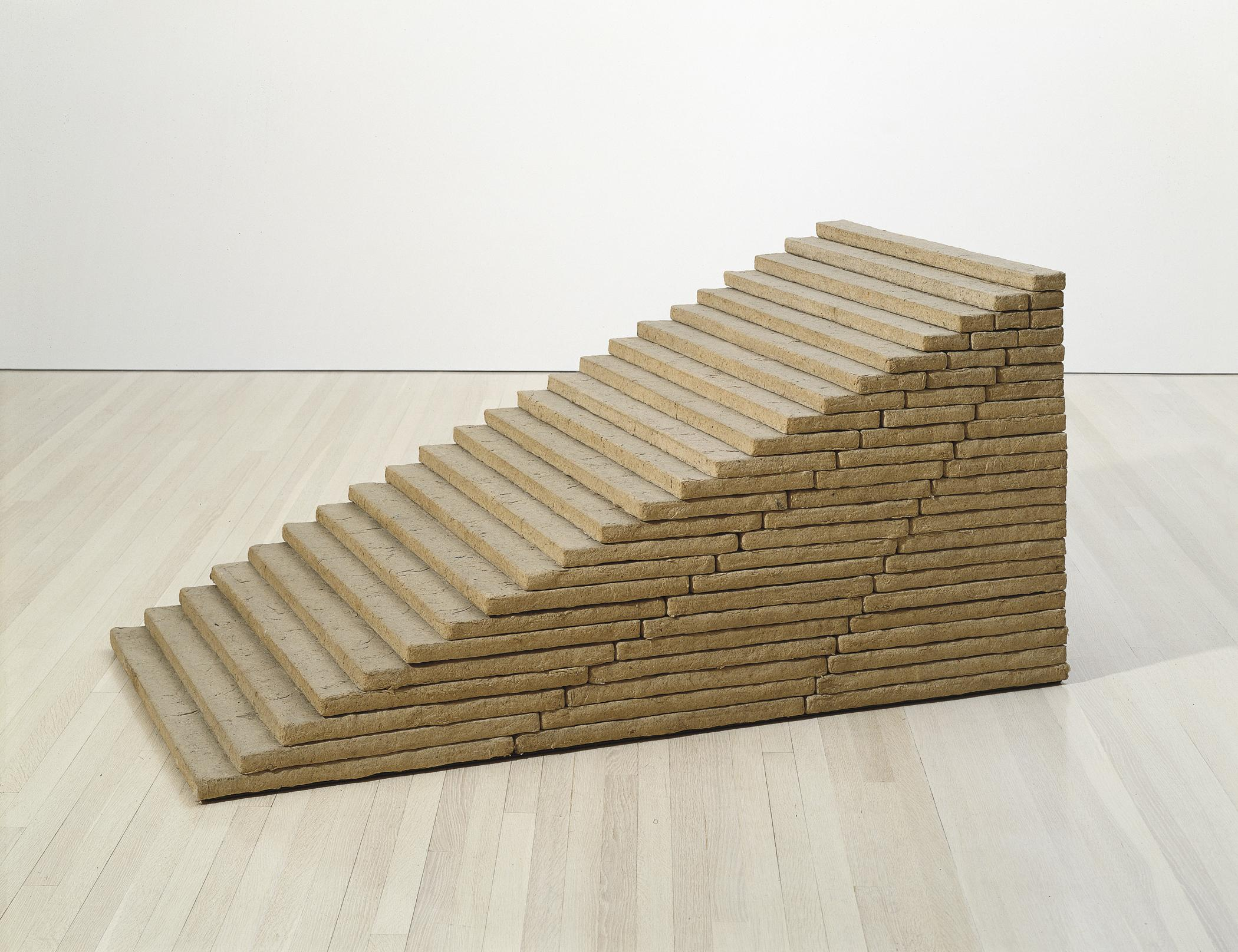 A short brown sculpture made of thin rectangular slabs stacked atop one another forming a twenty-three-step-high stairway sits on a hardwood floor in a gallery space.