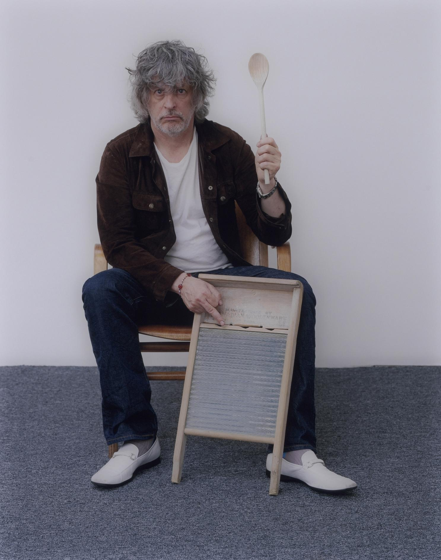 A light-skinned man with gray and disheveled chin-length hair sits on a chair, staring at the camera. In his left hand, he holds a long wooden spoon straight up in the air. His right middle finger is extended above a wood-and-metal washing board against his leg.