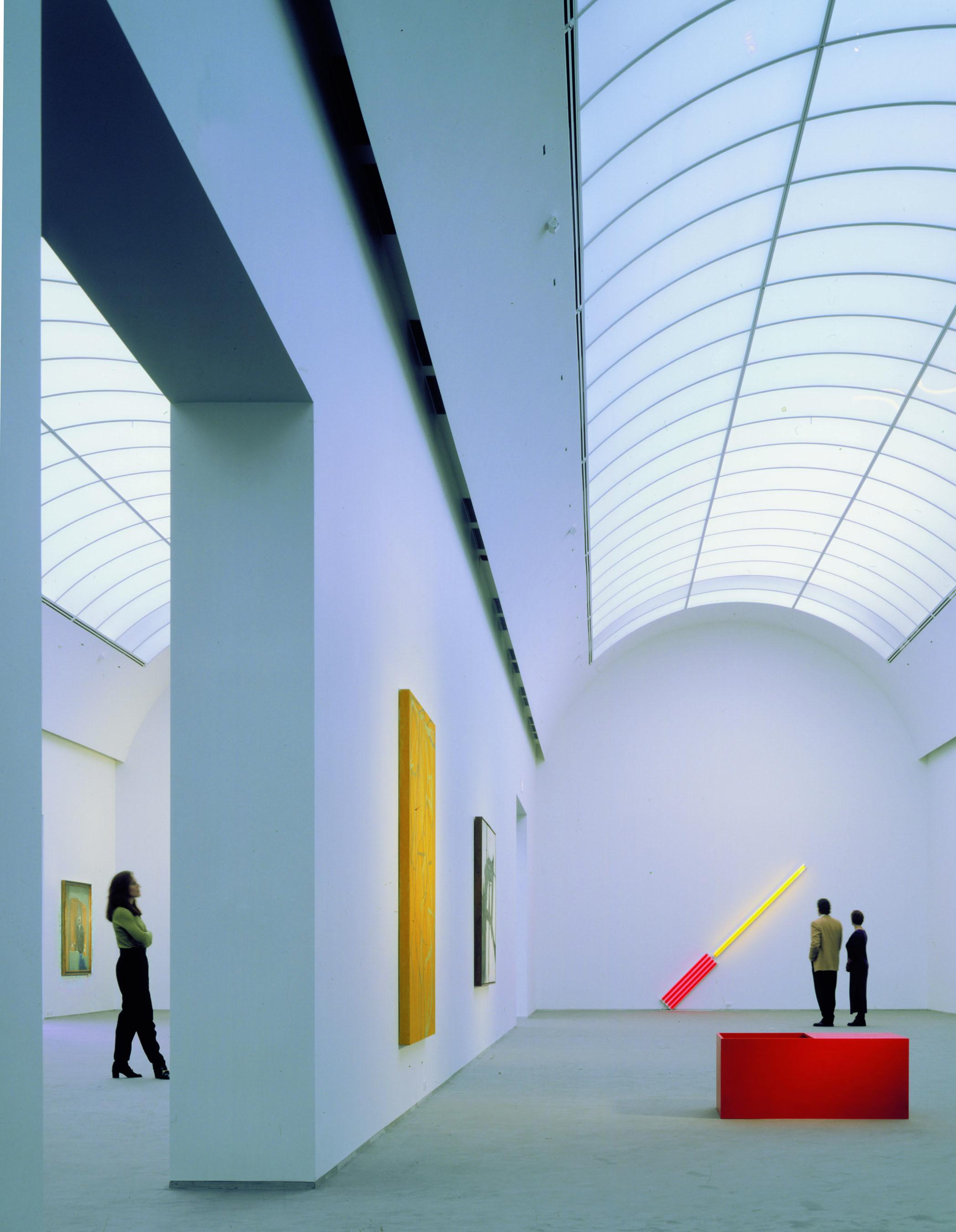 A light-filled gallery with white walls has a curved barrel vault ceiling and three visitors viewing artworks.