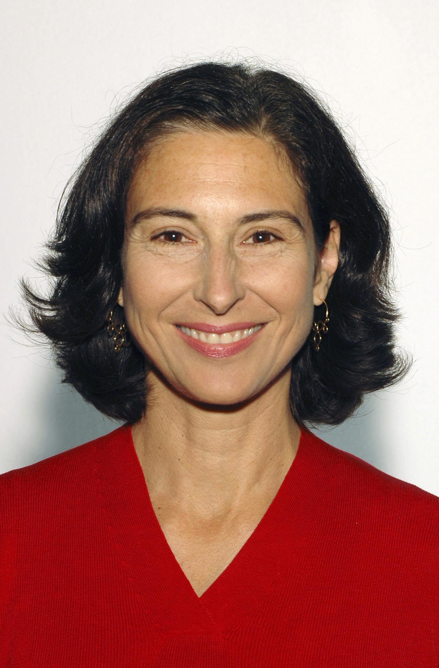 A middle-aged woman with dark shoulder-length hair wearing a red v-neck sweater smiles.