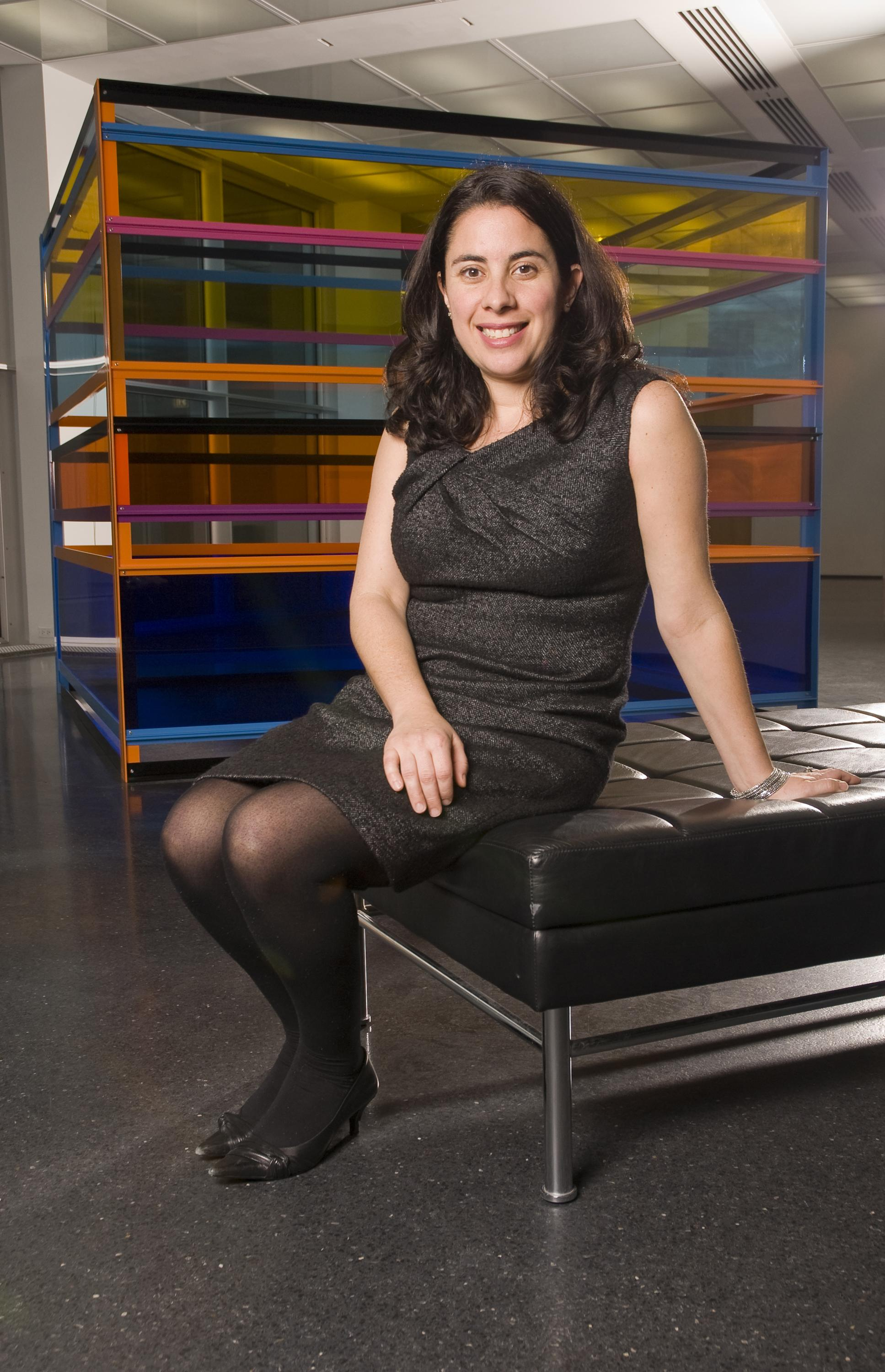 A woman with brown eyes and long brown hair in loose curls, wears a dark grey dress and sits on a black bench in front of a transparent cube with horizontal blocks of color.