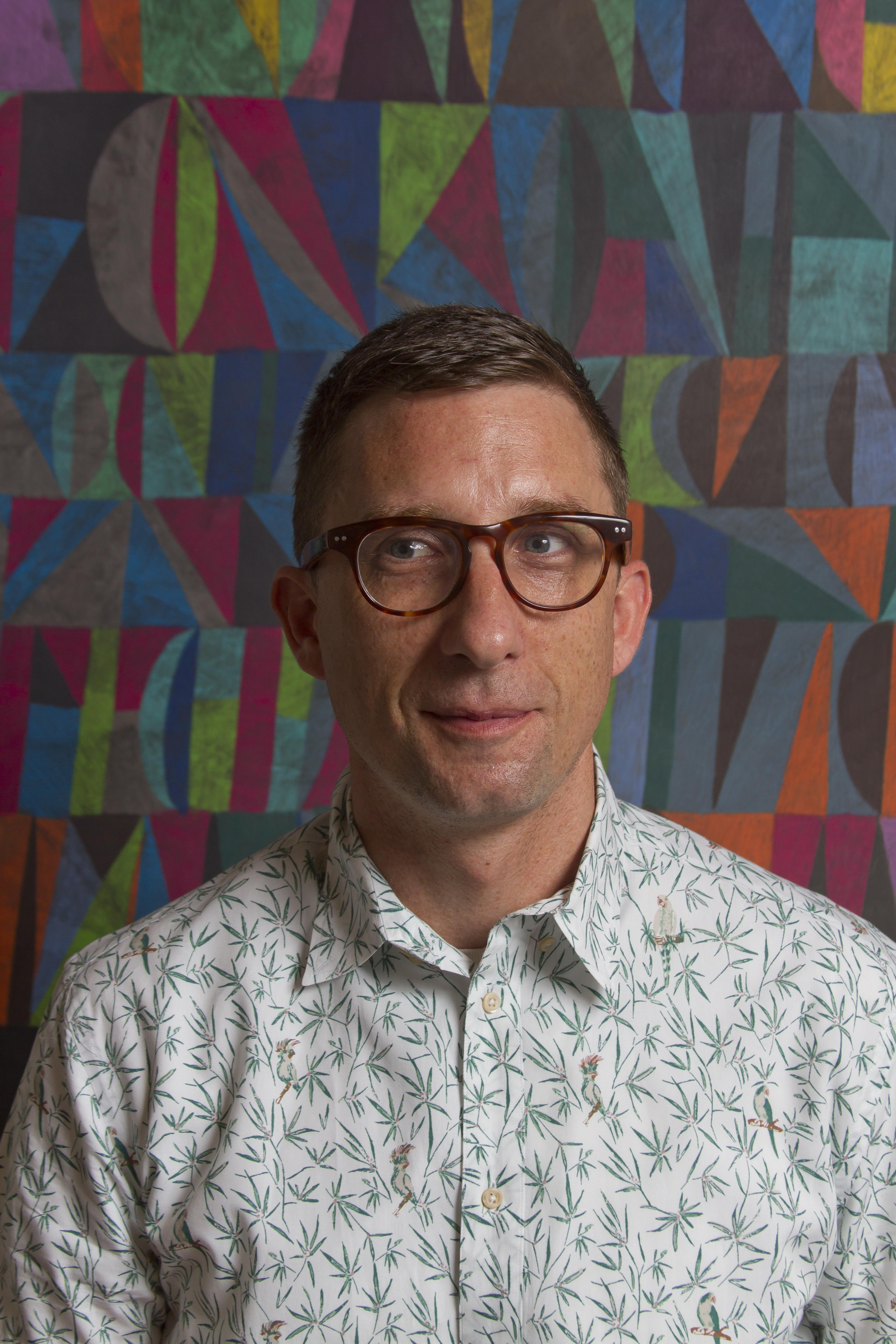 A light-skinned man with short brown hair, horn-rimmed tortoiseshell glasses, and leaf-patterned shirt, is in front of a multicolor abstract background.