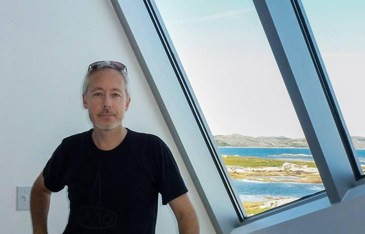 A light-skinned man with short white hair and stubble, wearing a black T-shirt with sun glasses on his head, stands by a window with a view of blue water and low mountains in the distance.