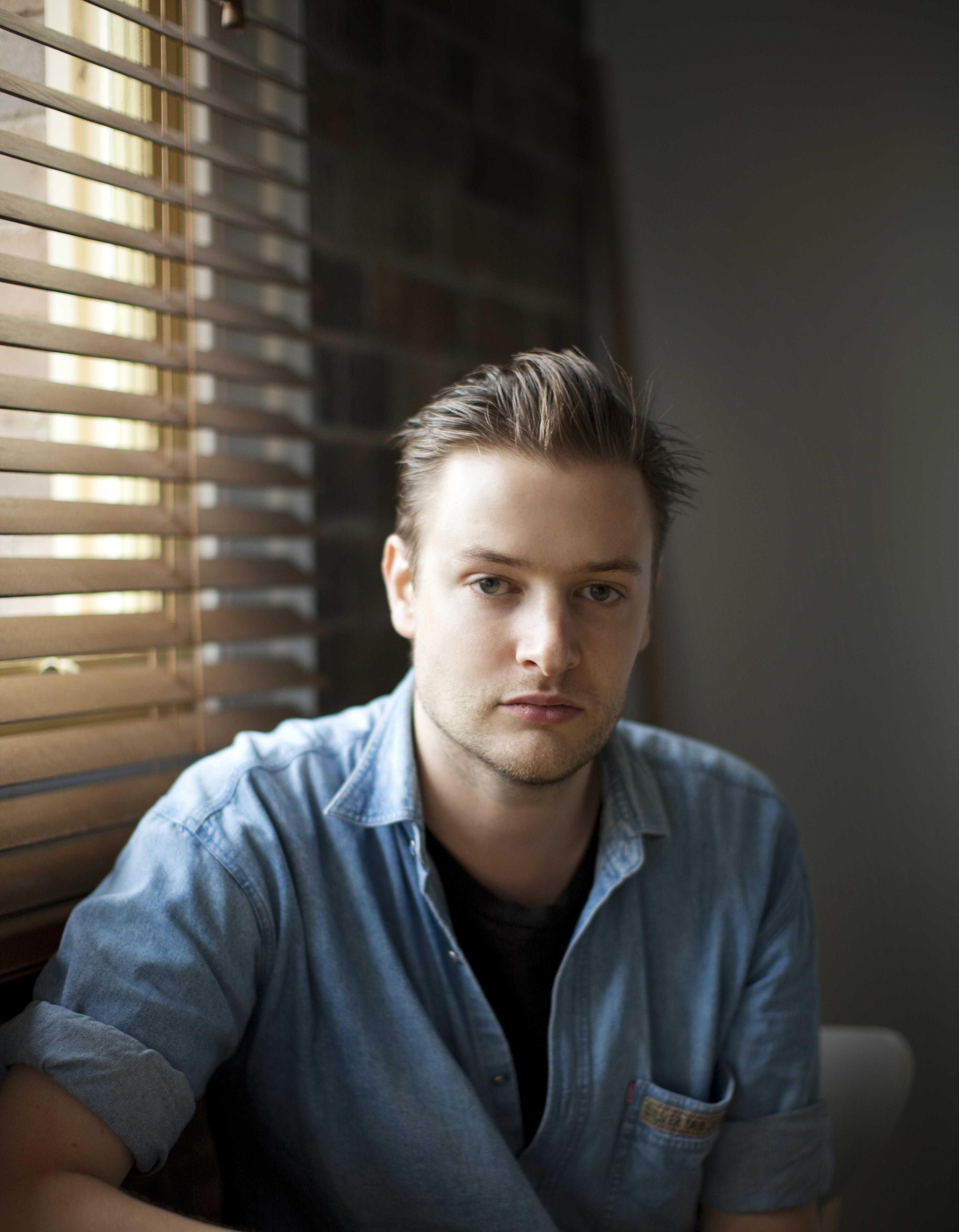 A light-skinned young man with slicked-back hair and faint stubble, wears a denim shirt.
