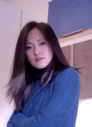 A young woman with Asian features and long, dark hair, wears a blue sweater and crosses her arms.