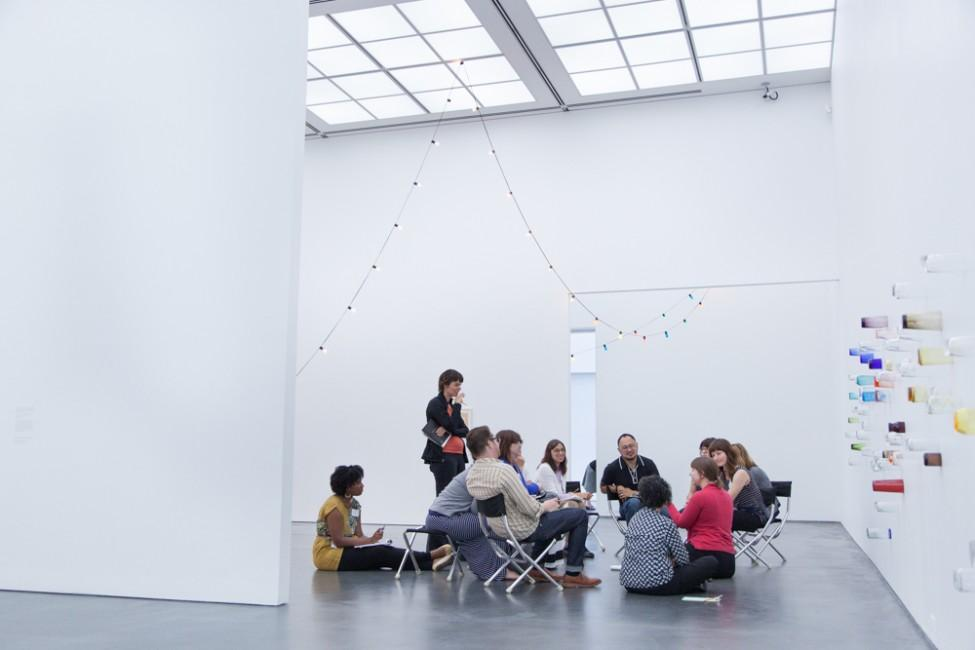 A group of twelve adults sit and talk in a bright white gallery with a delicate string of lights hung from the ceiling and multicolor cups fixed to the wall on the right.