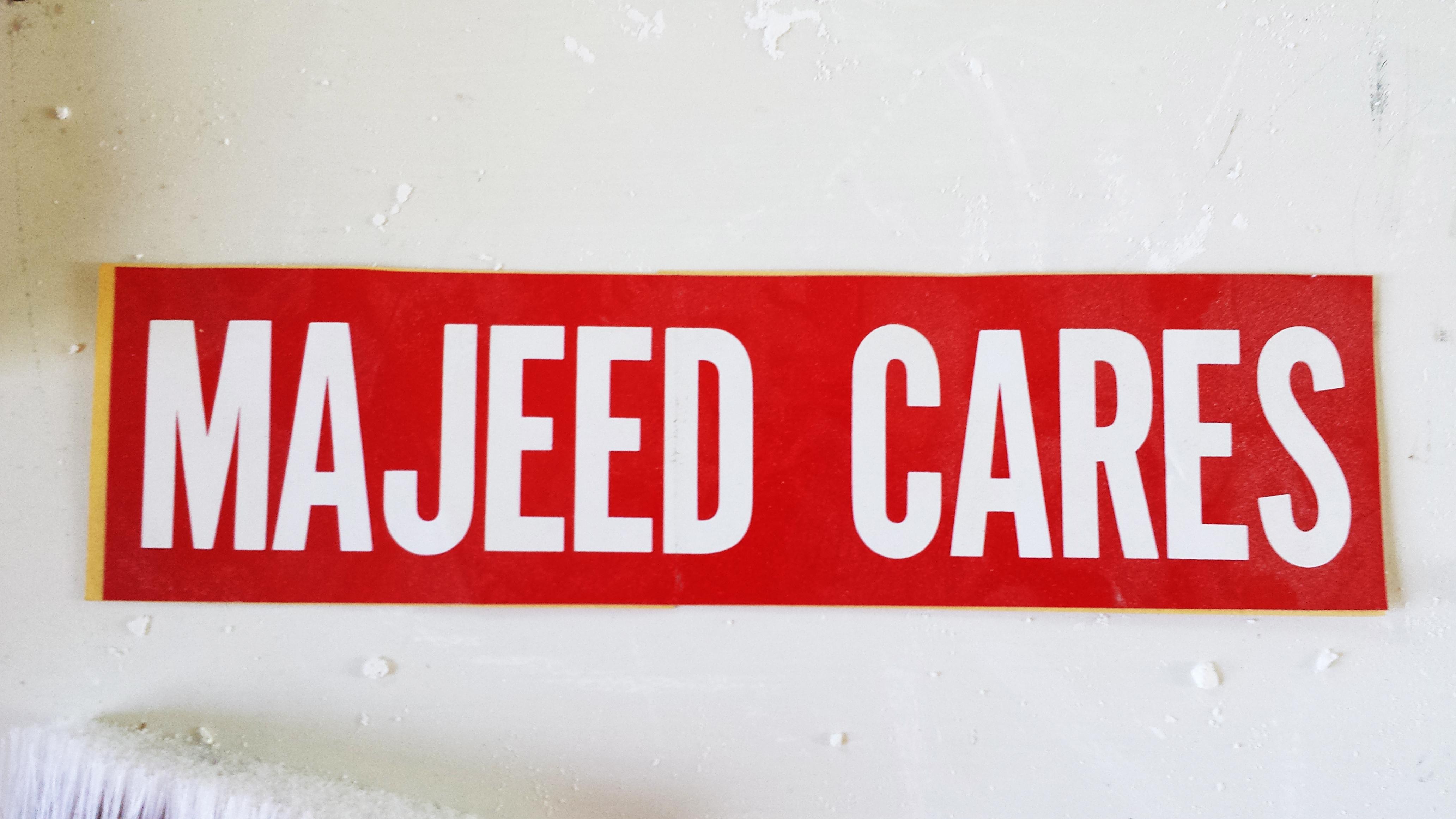 """A red bumper sticker with white text that reads """"Majeed Cares"""" lies on a white floor covered in flecks of white plaster and paint."""
