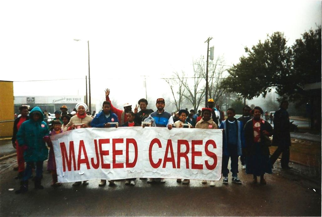 A small group stands in a street on a foggy day, holding a large sign that reads 'Majeed Cares.'