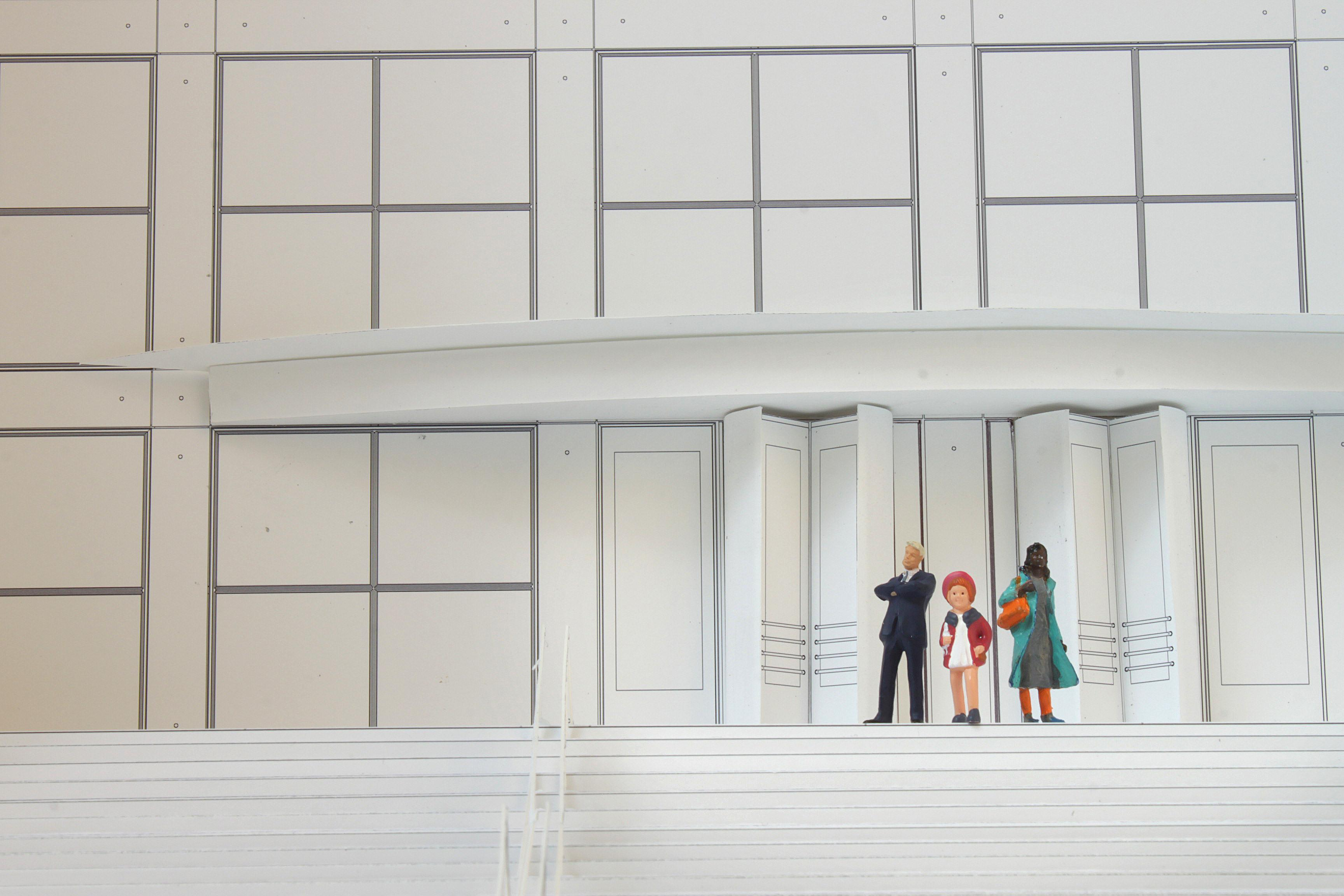 Black-and-white model of the MCA's front entrance with three figurines at the top of the stairs: a blond-haired man in a black suit; a child in a white dress, red jacket, and beret; and a black-haired woman in a grey dress and teal trench coat