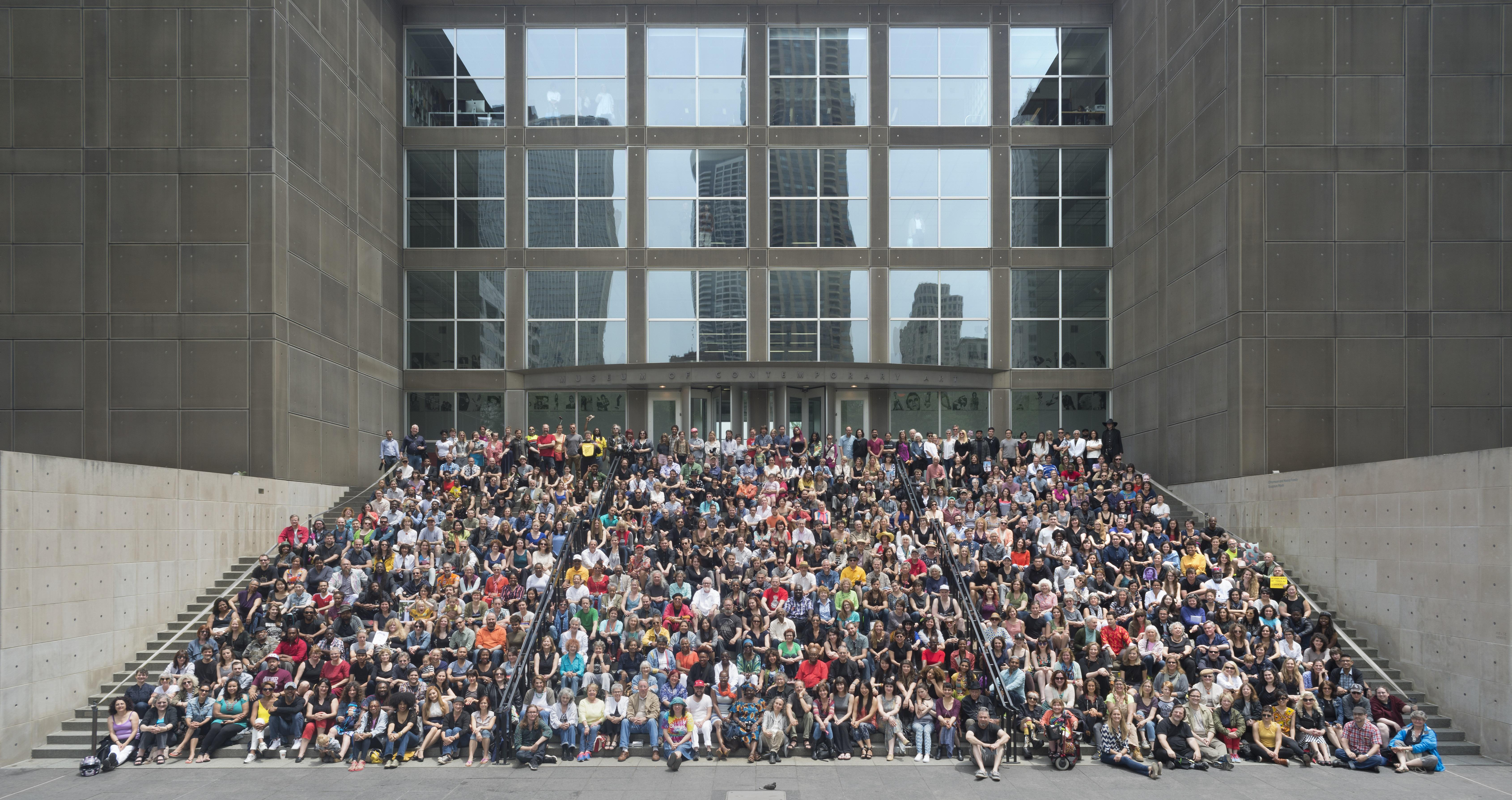 A large group fill the stairs for a photo in front of the entrance of MCA Chicago.